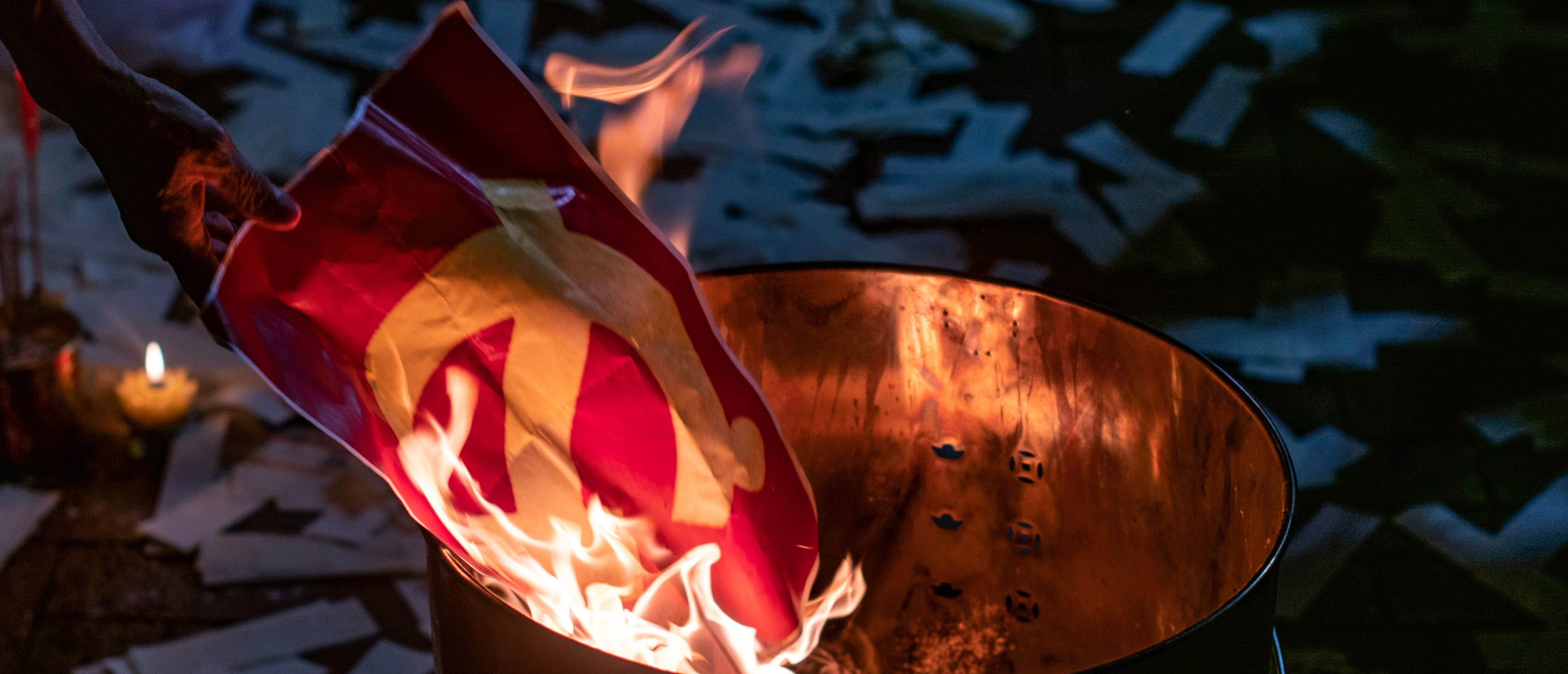 Pro-democracy activist Lui Yuk-lin (not pictured) burns the copy of a Communist hammer and sickle outside the Chinese liaison office in Hong Kong early on June 5, 2019, after the candlelight vigil to mark the 30th anniversary of the 1989 Tiananmen crackdown in Beijing. (Photo by Philip FONG / AFP) (Photo credit should read PHILIP FONG/AFP via Getty Images)