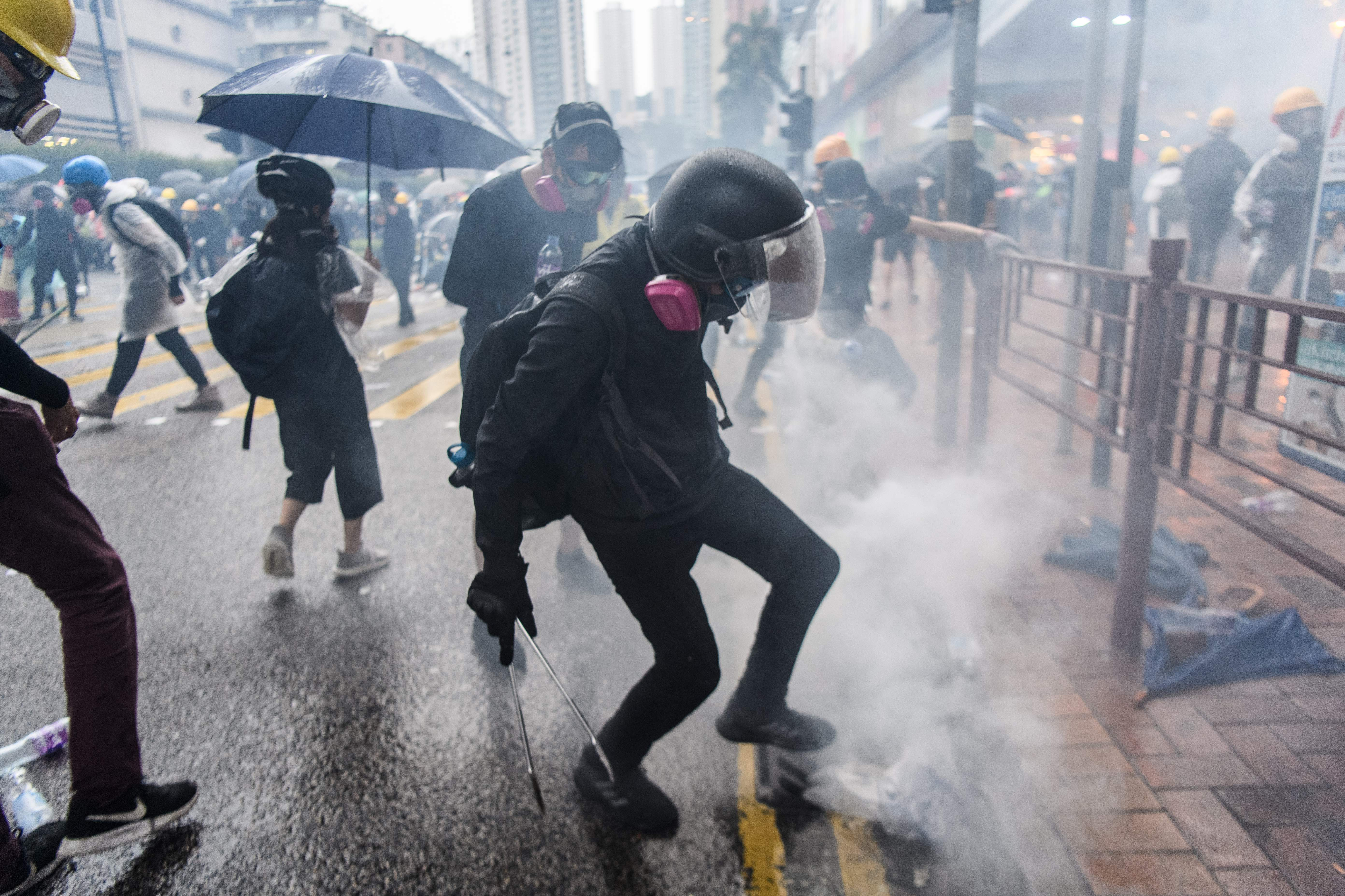 In this picture taken on August 25, 2019, a protester uses his foot to stamp a smoking tear gas round down a drain, after it was fired by police during a protest in Tsuen Wan, an area in the New Territories in Hong Kong. (Photo: Anthony Wallace/AFP via Getty Images)