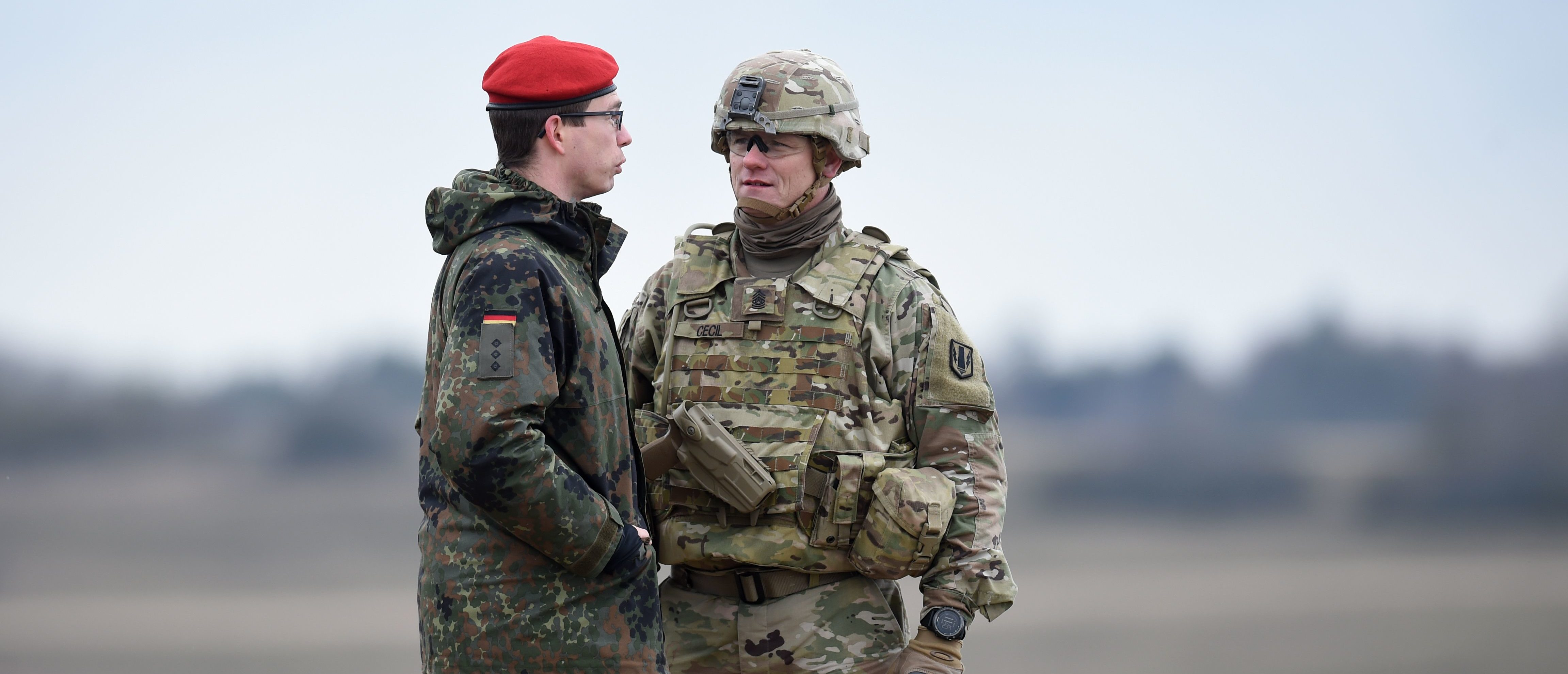 A Bundeswehr soldier (L) and an US soldier talk together during an artillery live fire event by the US Army Europe's 41st Field Artillery Brigade at the military training area in Grafenwoehr, southern Germany, on March 4, 2020. - The 41st Field Artillery Brigade plans, prepares, executes and assesses operations to provide US Army Europe with long-range precision strike capabilities. (Photo by Christof STACHE / AFP) (Photo by CHRISTOF STACHE/AFP via Getty Images)