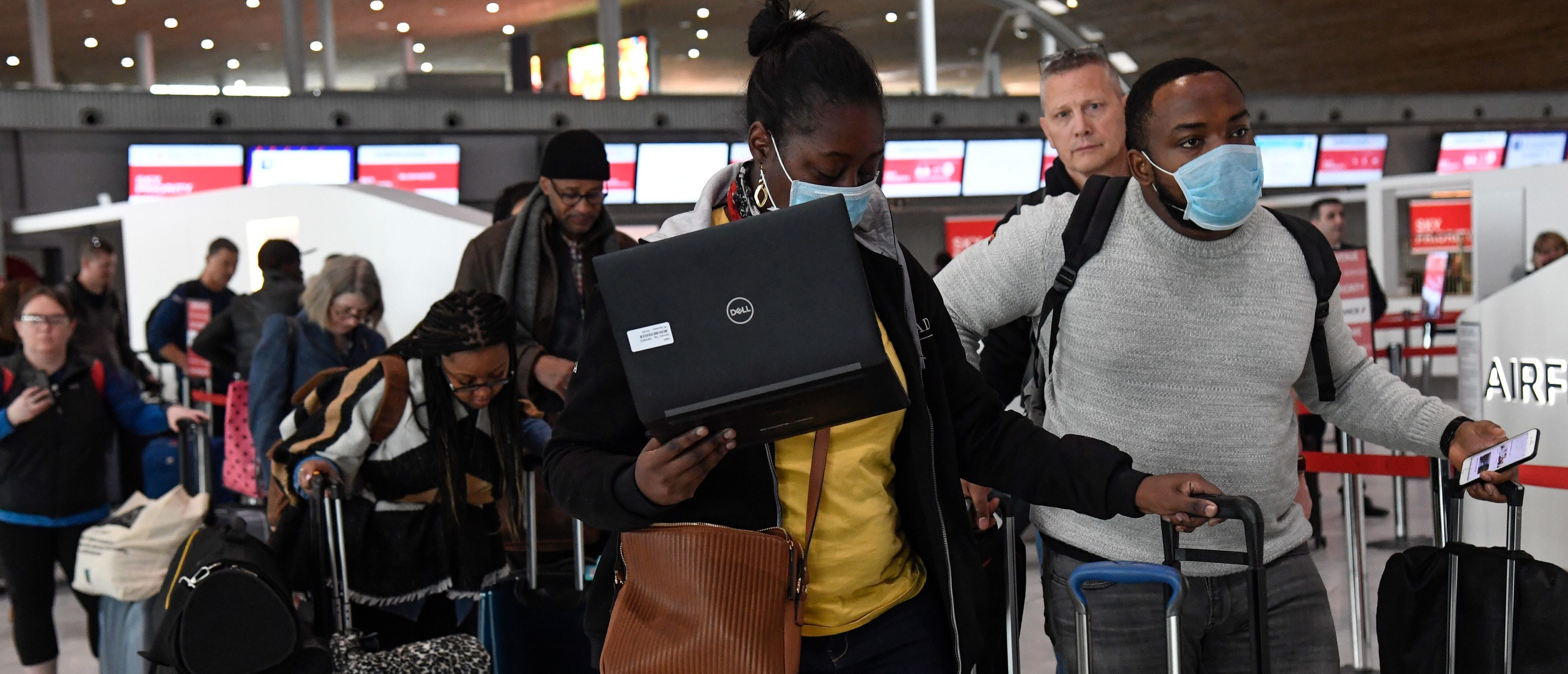 Travellers with protective face mask queue at an airport information desk at Paris-Charles-de-Gaulle airport after a US 30-day ban on travel from Europe due to the COVID-19 spread in Roissy-en-France on March 12, 2020. - US President Donald Trump announced on March 11, 2020 a shock 30-day ban on travel from mainland Europe over the coronavirus pandemic that has sparked unprecedented lockdowns, widespread panic and another financial market meltdown. (Photo by Bertrand GUAY / AFP) (Photo by BERTRAND GUAY/AFP via Getty Images)