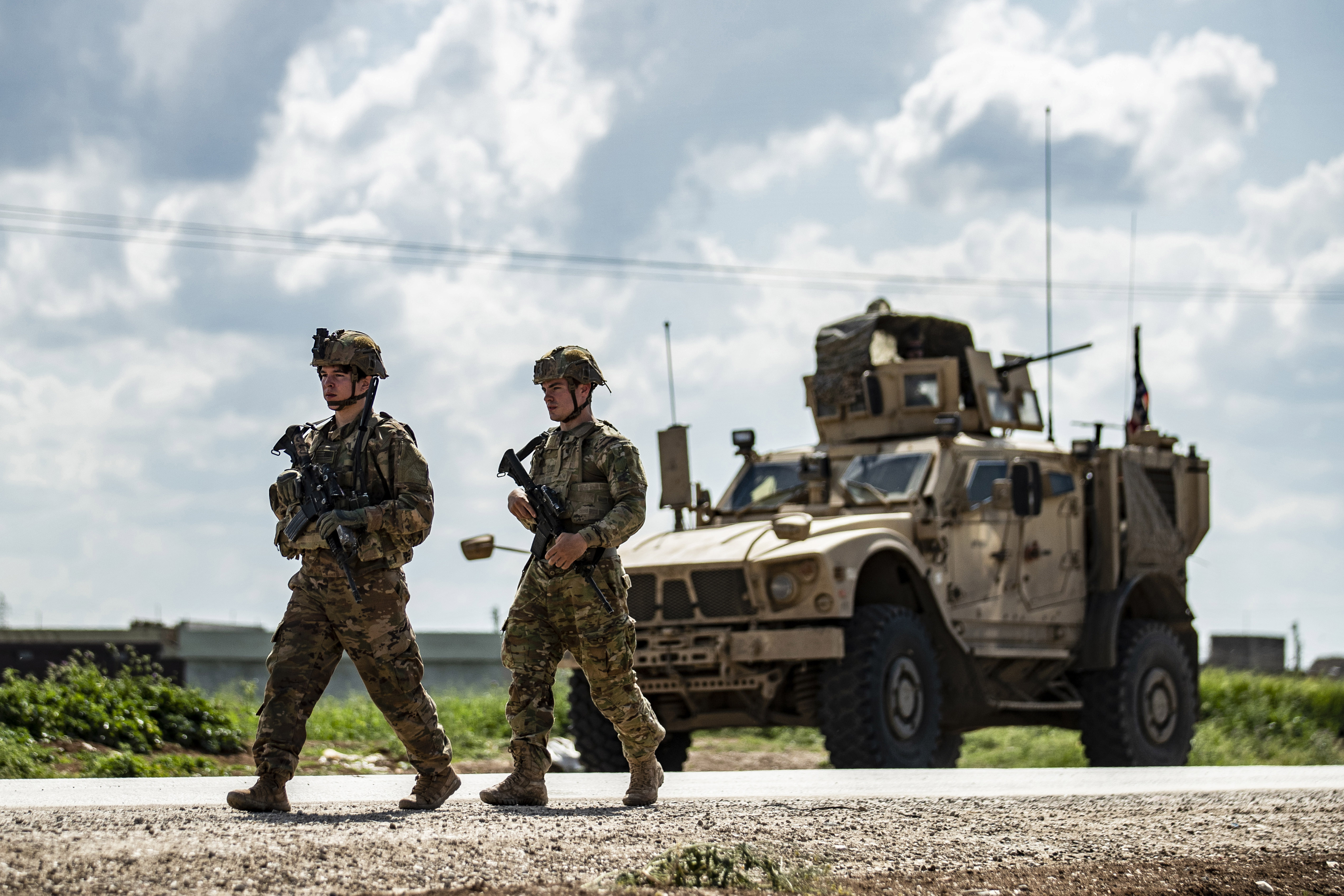 US soldiers walk along the side of a road across from a US military MRAP (Mine Resistant Ambush Protected) vehicle, near the village of Tannuriyah in the countryside east of Qamishli in Syria's northeastern Hasakah province on May 2, 2020. (Photo by DELIL SOULEIMAN/AFP via Getty Images)