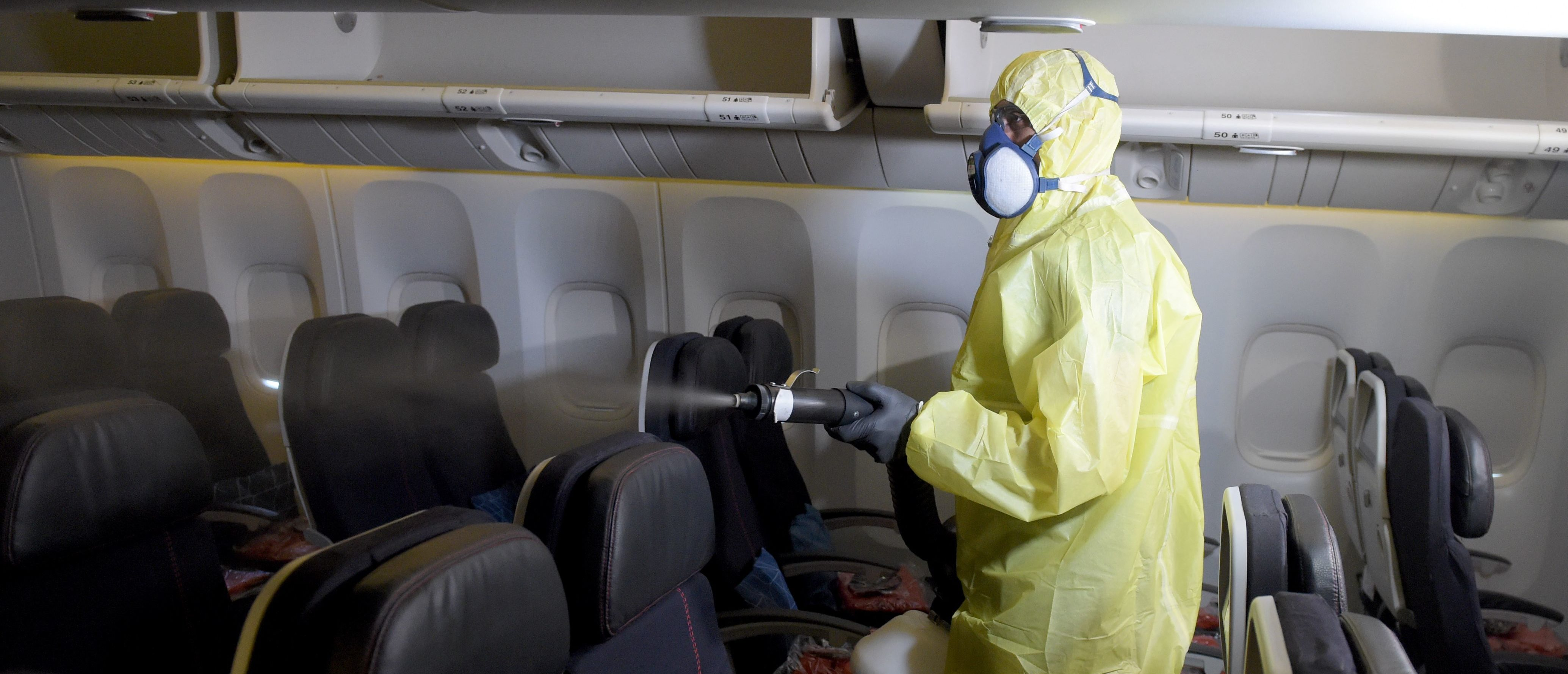 A worker disinfects the cabin area of an Air France aircraft at Roissy-Charles de Gaulle Airport on the outskirts of Paris on May 12, 2020. - As the world emerges from a lockdown situation, it is imperative for airlines survival that their clients return to the skies as soon as possible. This does not seem to be a foregone conclusion: only 14 per cent of consumers would get back on a plane as soon as traffic restrictions are lifted, 40 per cent would wait six months or more, and the majority would wait one or two months, according to a survey conducted in 11 countries by the International Air Transport Association (IATA), which groups 290 airlines. (Photo by ERIC PIERMONT / AFP) (Photo by ERIC PIERMONT/AFP via Getty Images)