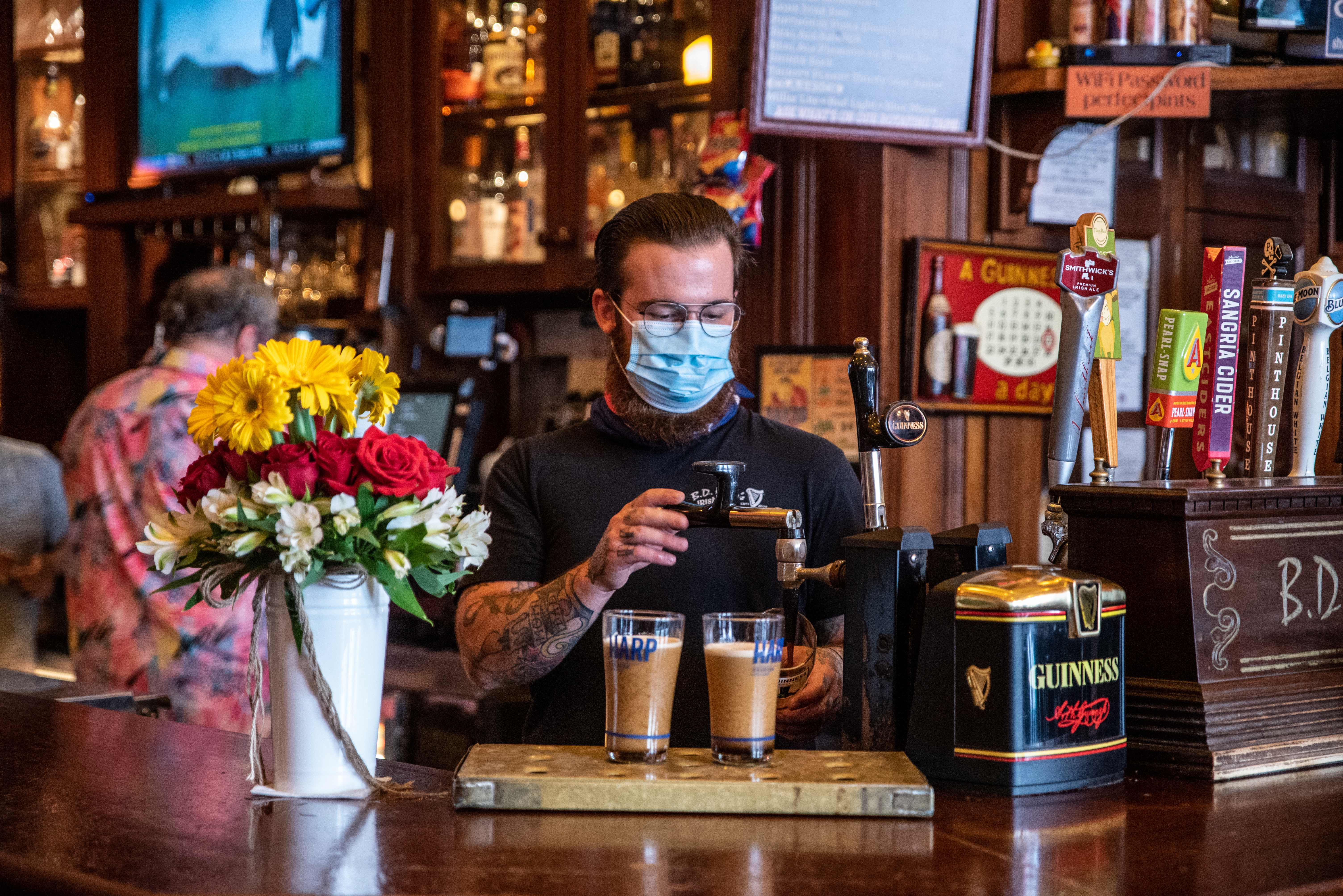 A bartender pours drinks for customers at a bar in Austin, Texas on May 22, 2020. (Photo by SERGIO FLORES/AFP via Getty Images)