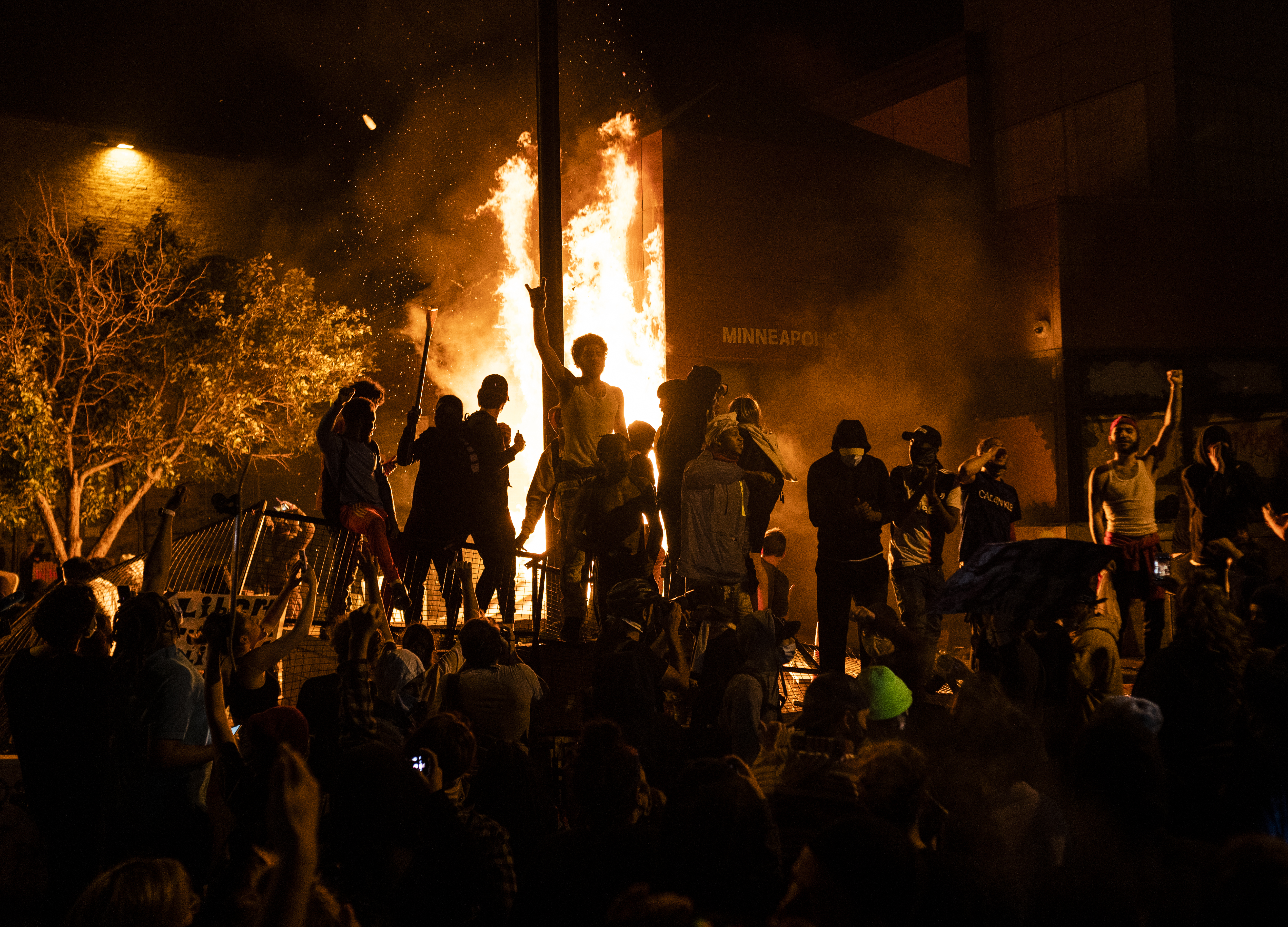 Protesters cheer as the Third Police Precinct burns behind them on May 28, 2020 in Minneapolis, Minnesota. (Photo by Stephen Maturen/Getty Images)