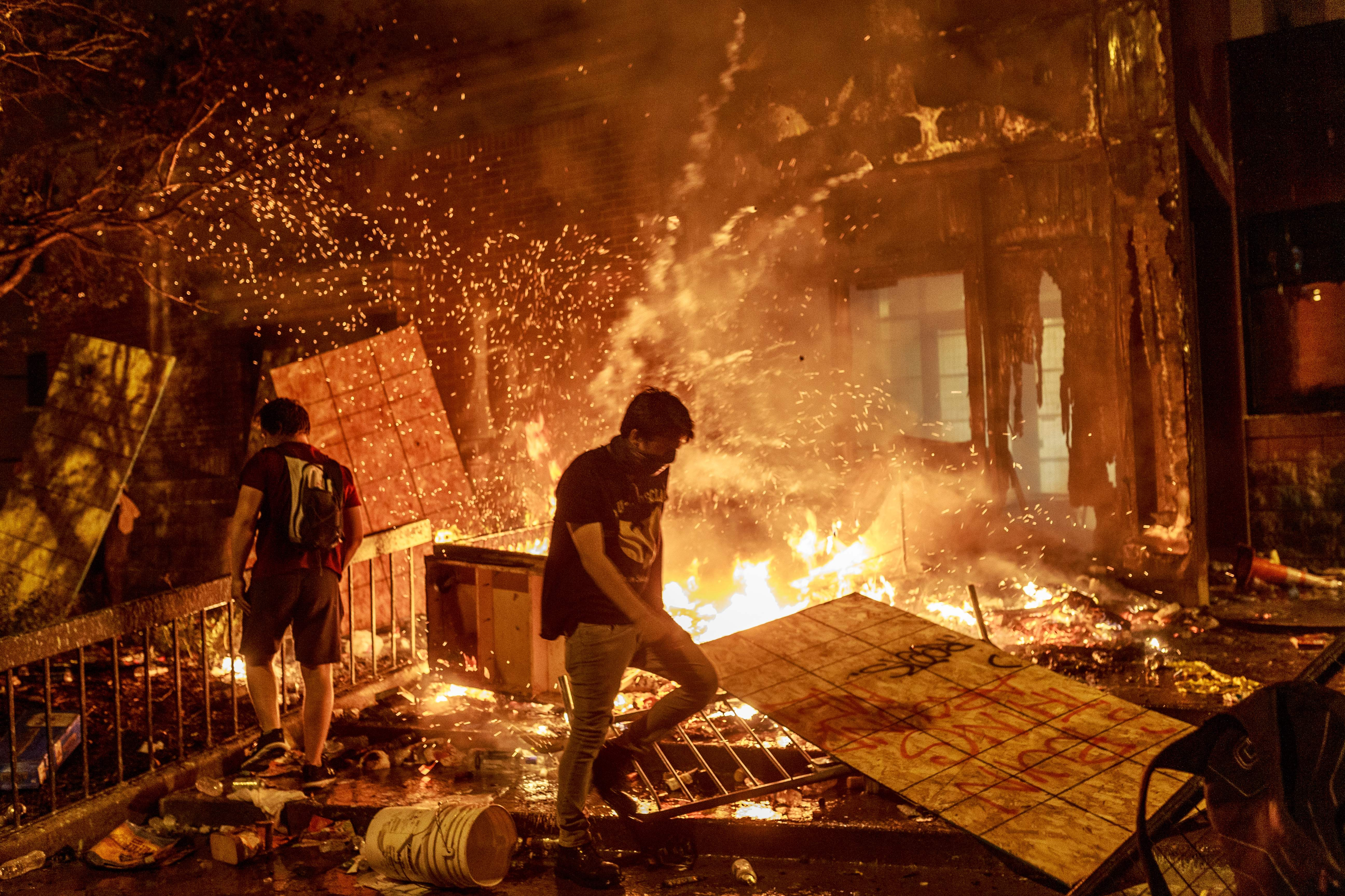 Protesters walk past burning debris outside the Third Police Precinct on May 28, 2020 in Minneapolis, Minnesota, during a protest over the death of George Floyd. (Photo by KEREM YUCEL/AFP via Getty Images)