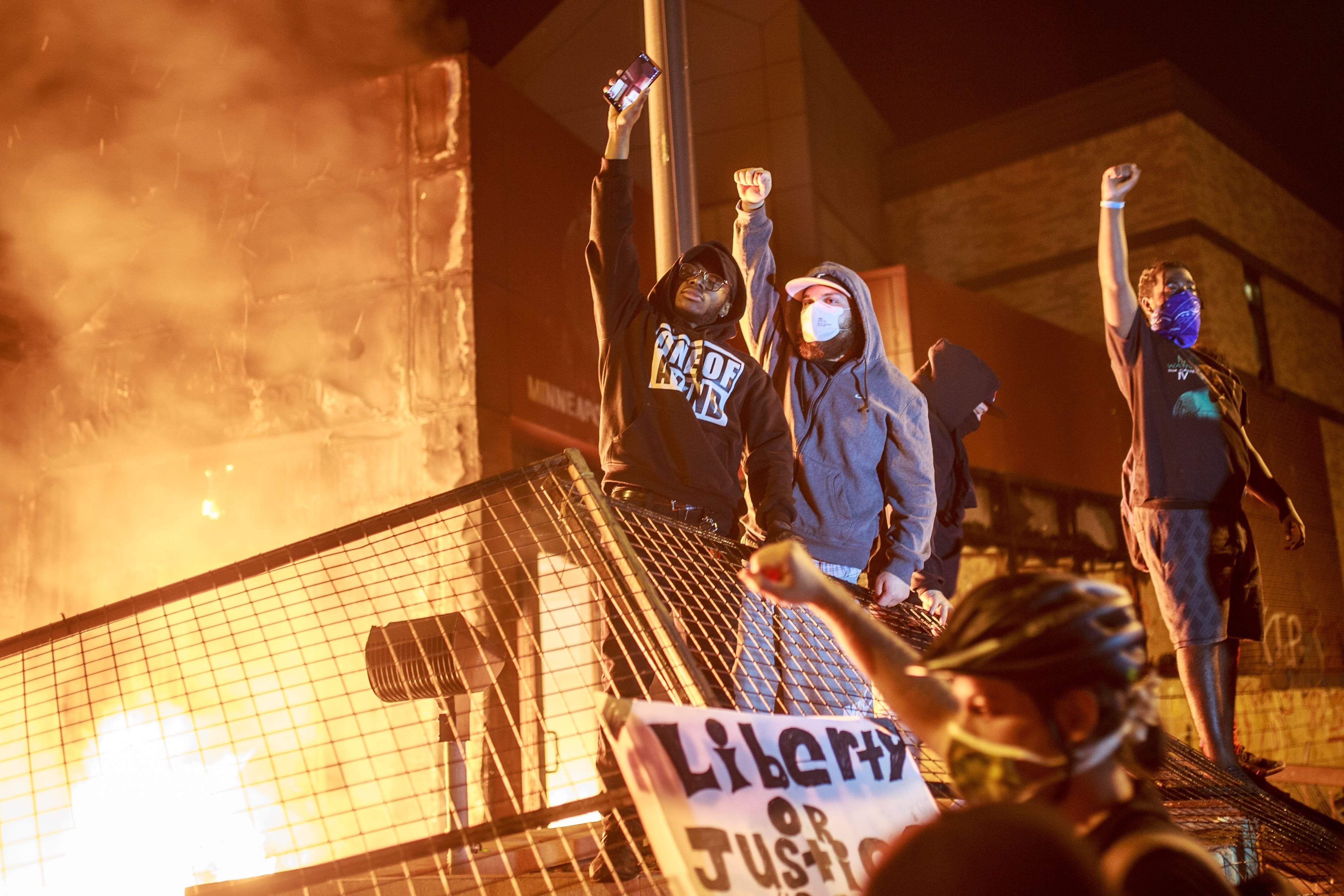 Protesters hold up their fists as flames rise behind them in front of the Third Police Precinct on May 28, 2020 in Minneapolis, Minnesota, during a protest over the death of George Floyd, an unarmed black man, who died after a police officer kneeled on his neck for several minutes. - A police precinct in Minnesota went up in flames late on May 28 in a third day of demonstrations as the so-called Twin Cities of Minneapolis and St. Paul seethed over the shocking police killing of a handcuffed black man. The precinct, which police had abandoned, burned after a group of protesters pushed through barriers around the building, breaking windows and chanting slogans. A much larger crowd demonstrated as the building went up in flames. (Photo by Kerem Yucel / AFP) (Photo by KEREM YUCEL/AFP via Getty Images)