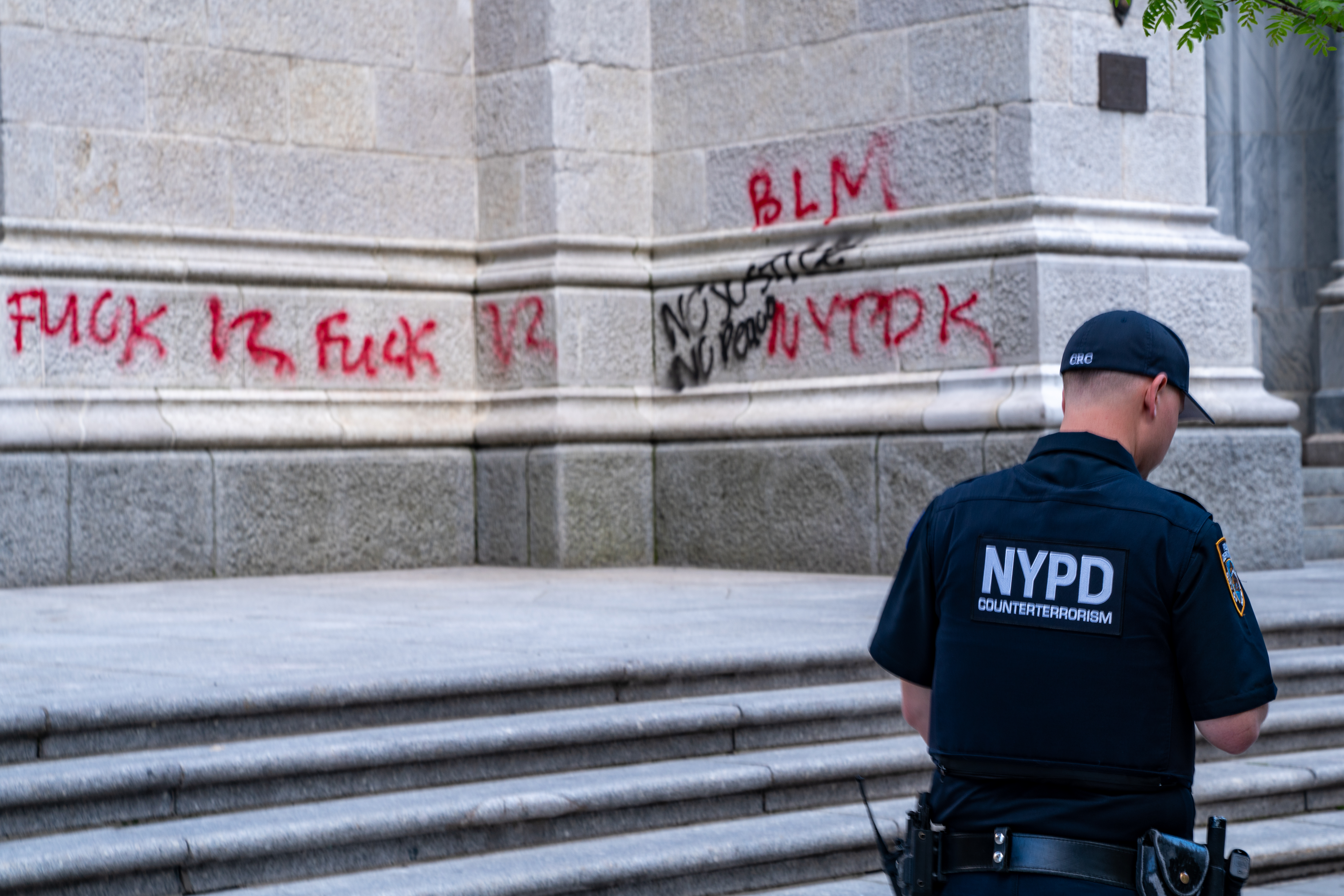 An NYPD officer walks by a vandalized St. Patrick's Cathedral on May 30, 2020 in New York City. (Photo by David Dee Delgado/Getty Images)