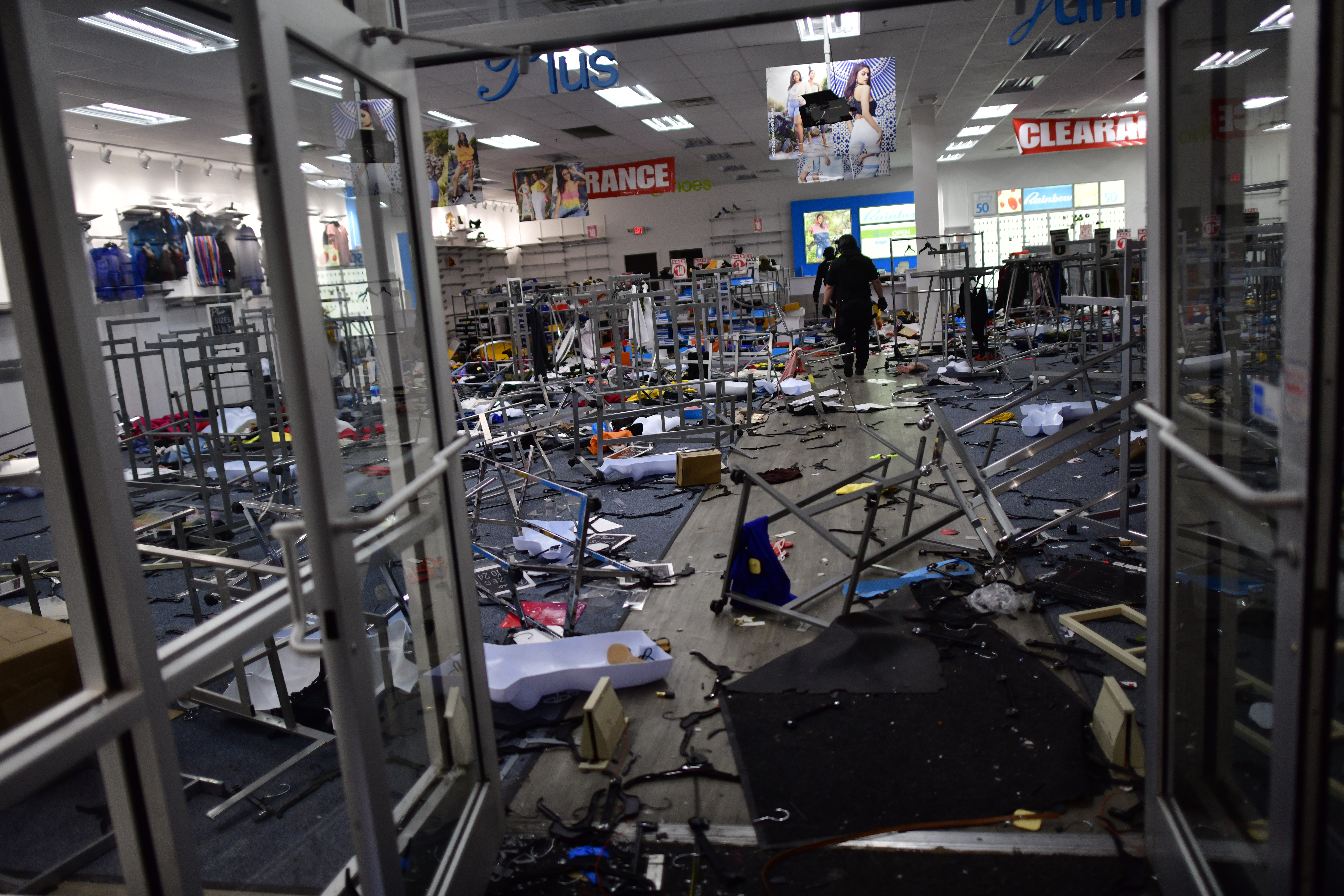 Police investigate a looted clothing store during widespread unrest following the death of George Floyd on May 31, 2020 in Philadelphia, Pennsylvania. (Photo by Mark Makela/Getty Images)