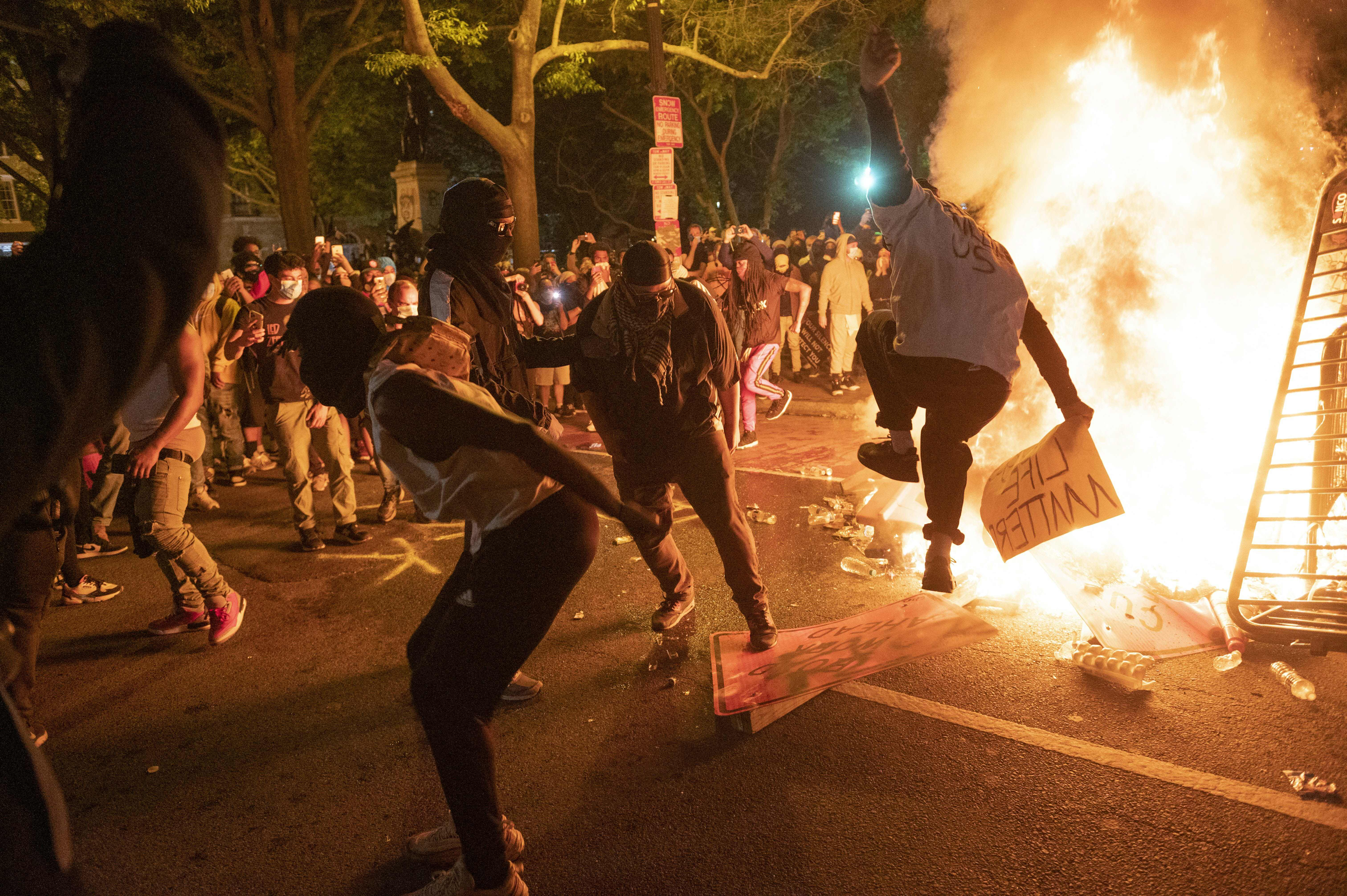 Protesters jump on a street sign near a burning barricade during a demonstration against the death of George Floyd near the White House on May 31, 2020 in Washington, DC. - Thousands of National Guard troops patrolled major US cities after five consecutive nights of protests over racism and police brutality that boiled over into arson and looting, sending shock waves through the country. The death Monday of an unarmed black man, George Floyd, at the hands of police in Minneapolis ignited this latest wave of outrage in the US over law enforcement's repeated use of lethal force against African Americans -- this one like others before captured on cellphone video. (Photo by ROBERTO SCHMIDT/AFP via Getty Images)