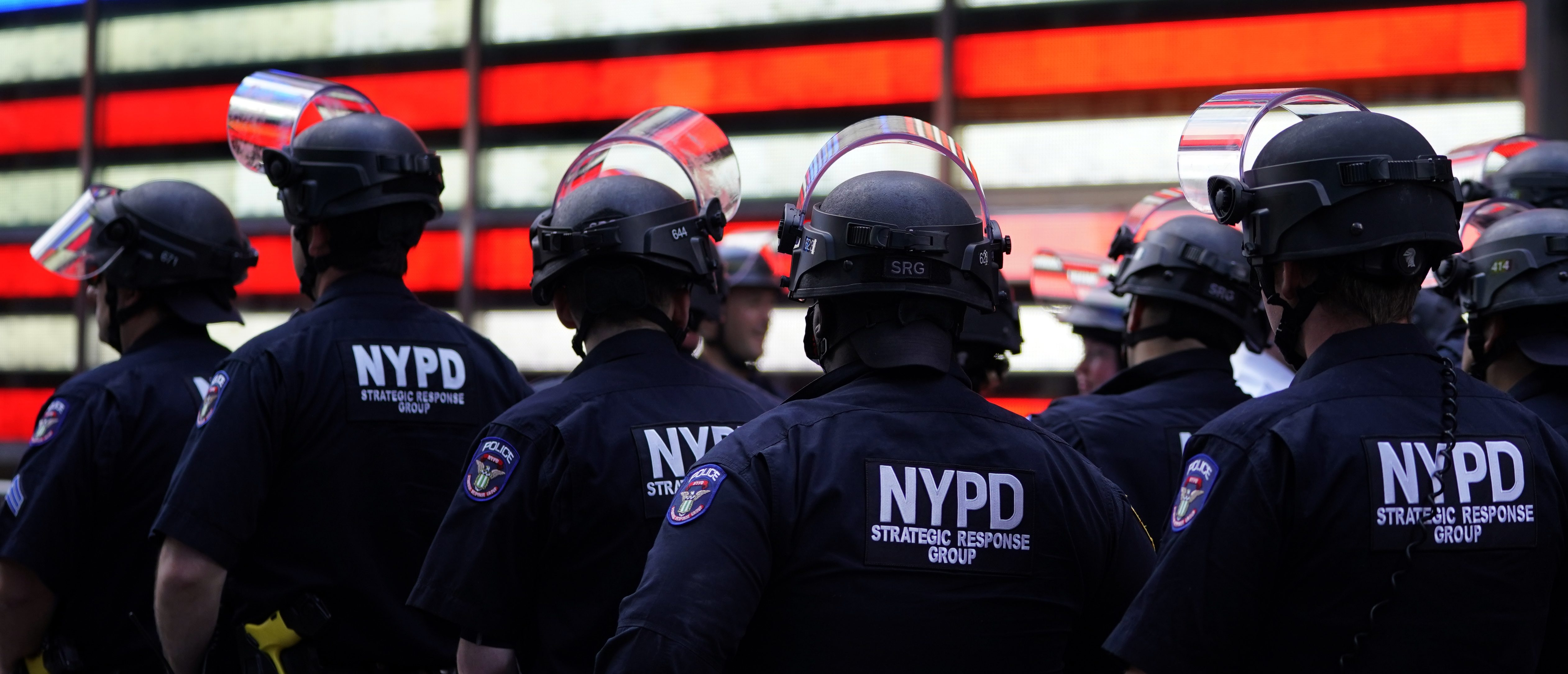 """TOPSHOT - NYPD police officers watch demonstrators in Times Square on June 1, 2020, during a """"Black Lives Matter"""" protest. - New York's mayor Bill de Blasio today declared a city curfew from 11:00 pm to 5:00 am, as sometimes violent anti-racism protests roil communities nationwide. Saying that """"we support peaceful protest,"""" De Blasio tweeted he had made the decision in consultation with the state's governor Andrew Cuomo, following the lead of many large US cities that instituted curfews in a bid to clamp down on violence and looting. (Photo by TIMOTHY A. CLARY / AFP) (Photo by TIMOTHY A. CLARY/AFP via Getty Images)"""