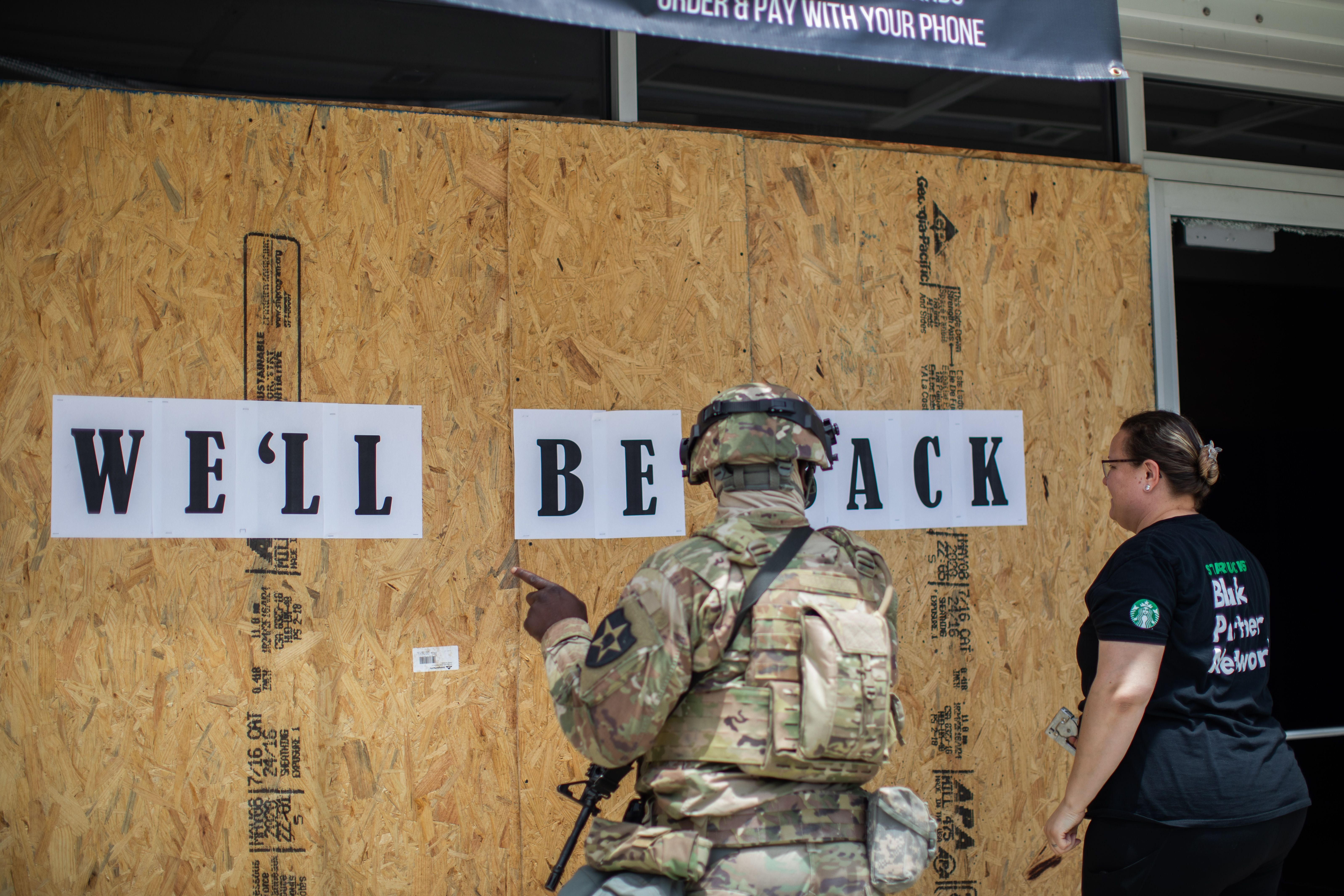 National Guard talks to a worker in front of a boarded up coffee shop in Downtown Long Beach, California on June 1, 2020, after a night of protests and looting. (Photo by APU GOMES/AFP via Getty Images)