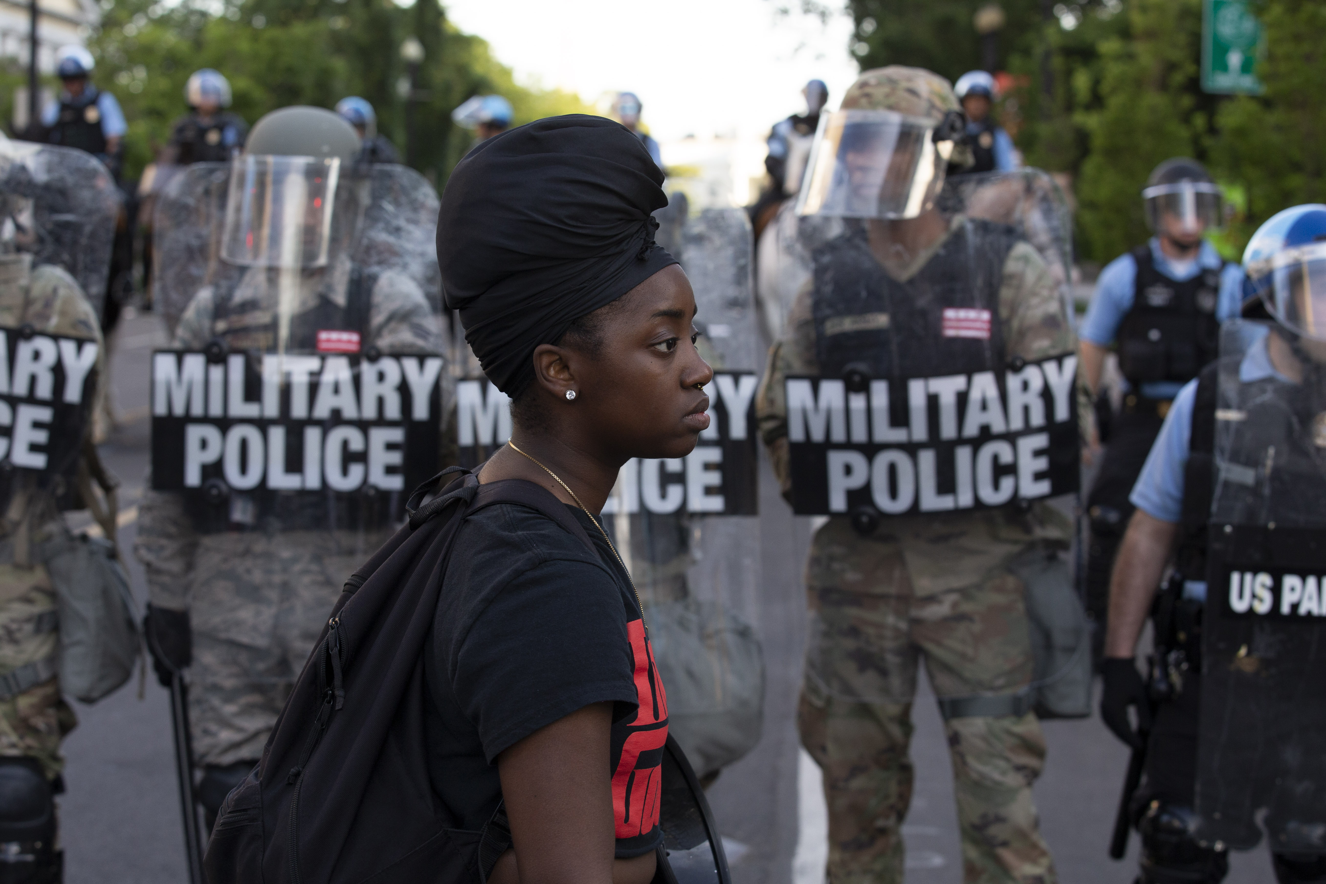 A demonstrator walks in front of a row of military police members wearing riot gear as they push back demonstrators outside of the White House, June 1, 2020 in Washington D.C., during a protest over the death of George Floyd, an unarmed black man, who died after a police officer kneeled on his neck for several minutes.(Photo by JOSE LUIS MAGANA/AFP via Getty Images)