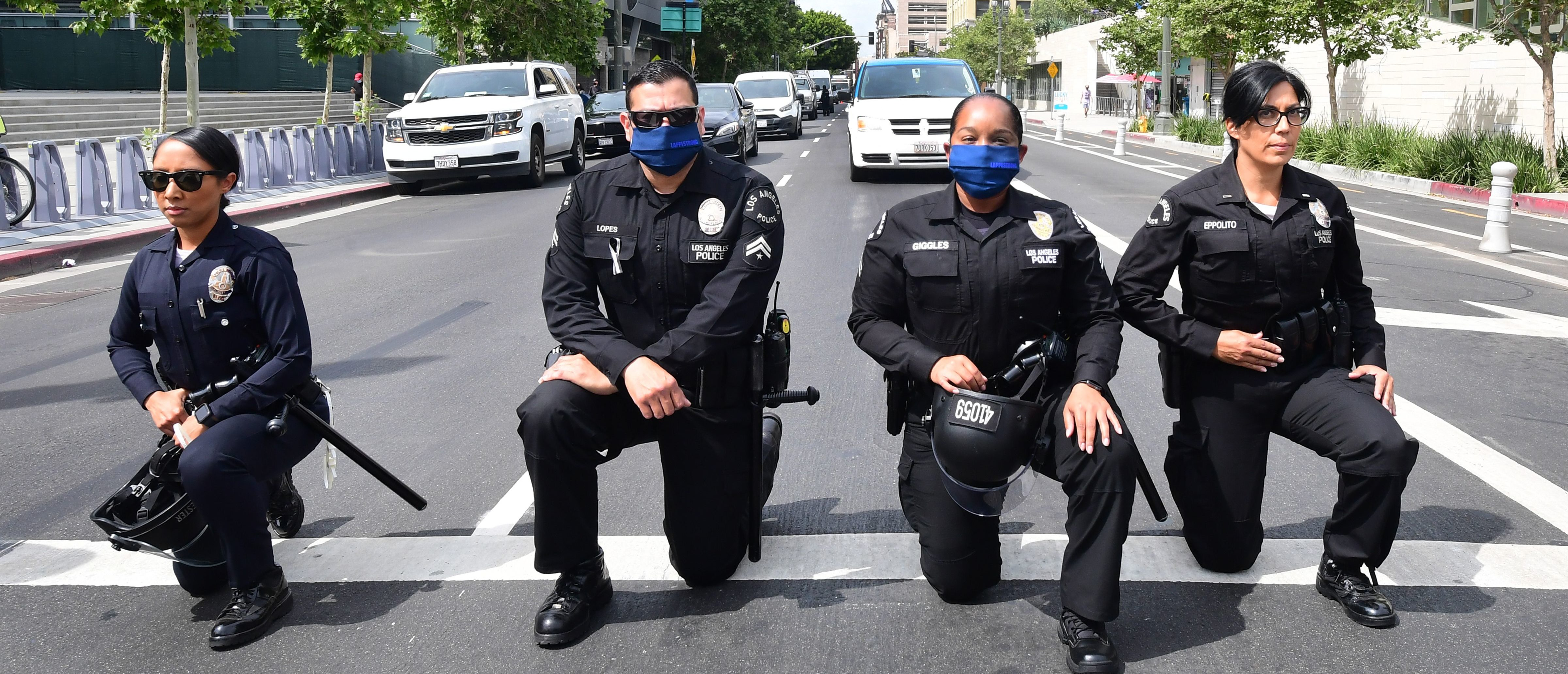 TOPSHOT - Los Angeles Police Department officers kneel during a rally led by Baptist Ministers to City Hall on June 2, 2020 in memory of George Floyd. - Anti-racism protests have put several US cities under curfew to suppress rioting, following the death of George Floyd while in police custody. (Photo by Frederic J. BROWN / AFP) (Photo by FREDERIC J. BROWN/AFP via Getty Images)