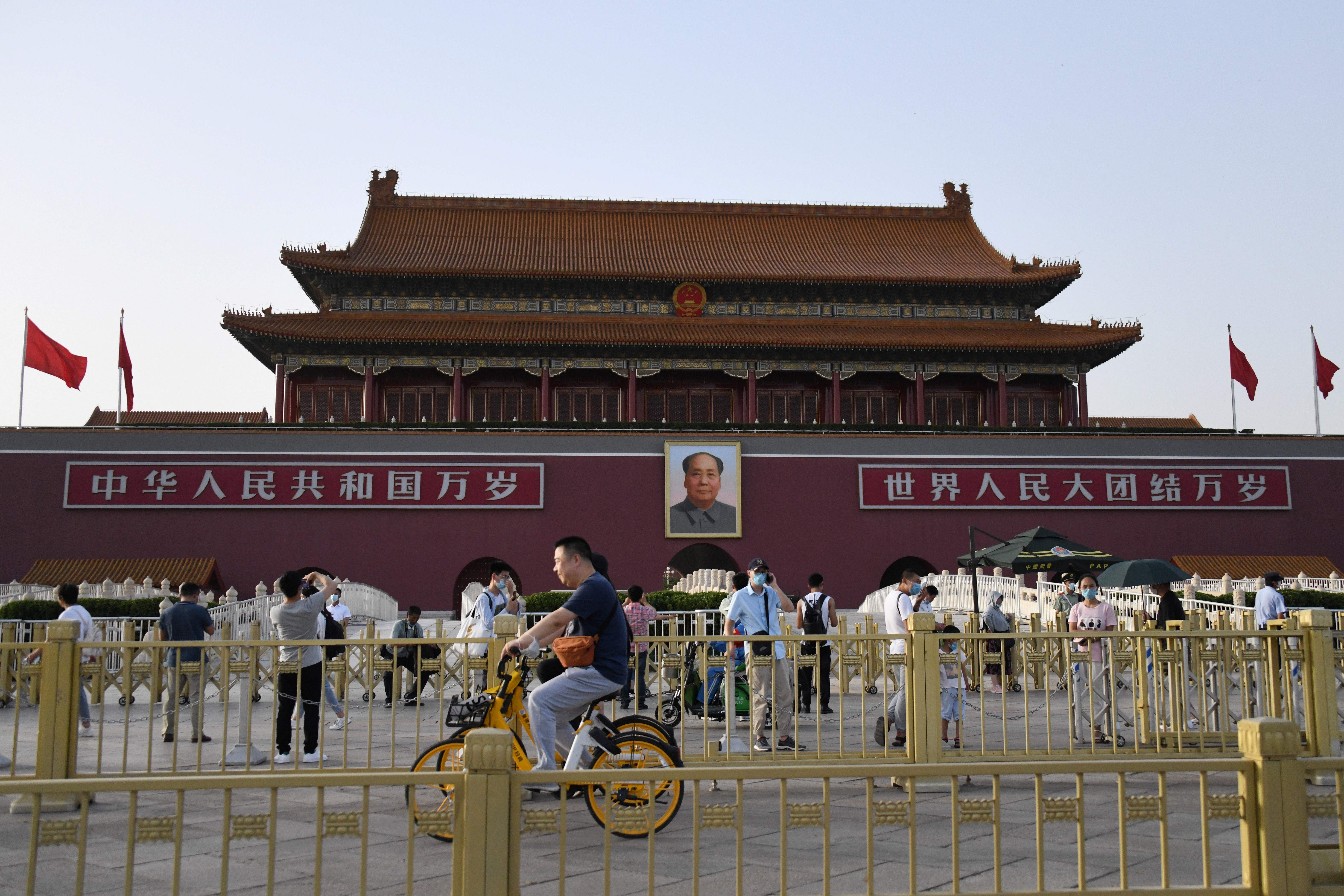 People cycle past Tiananmen gate on the eve of the 31st anniversary of the June 4, 1989 crackdown on pro-democracy protests, in Beijing on June 3, 2020. (Photo by GREG BAKER/AFP via Getty Images)