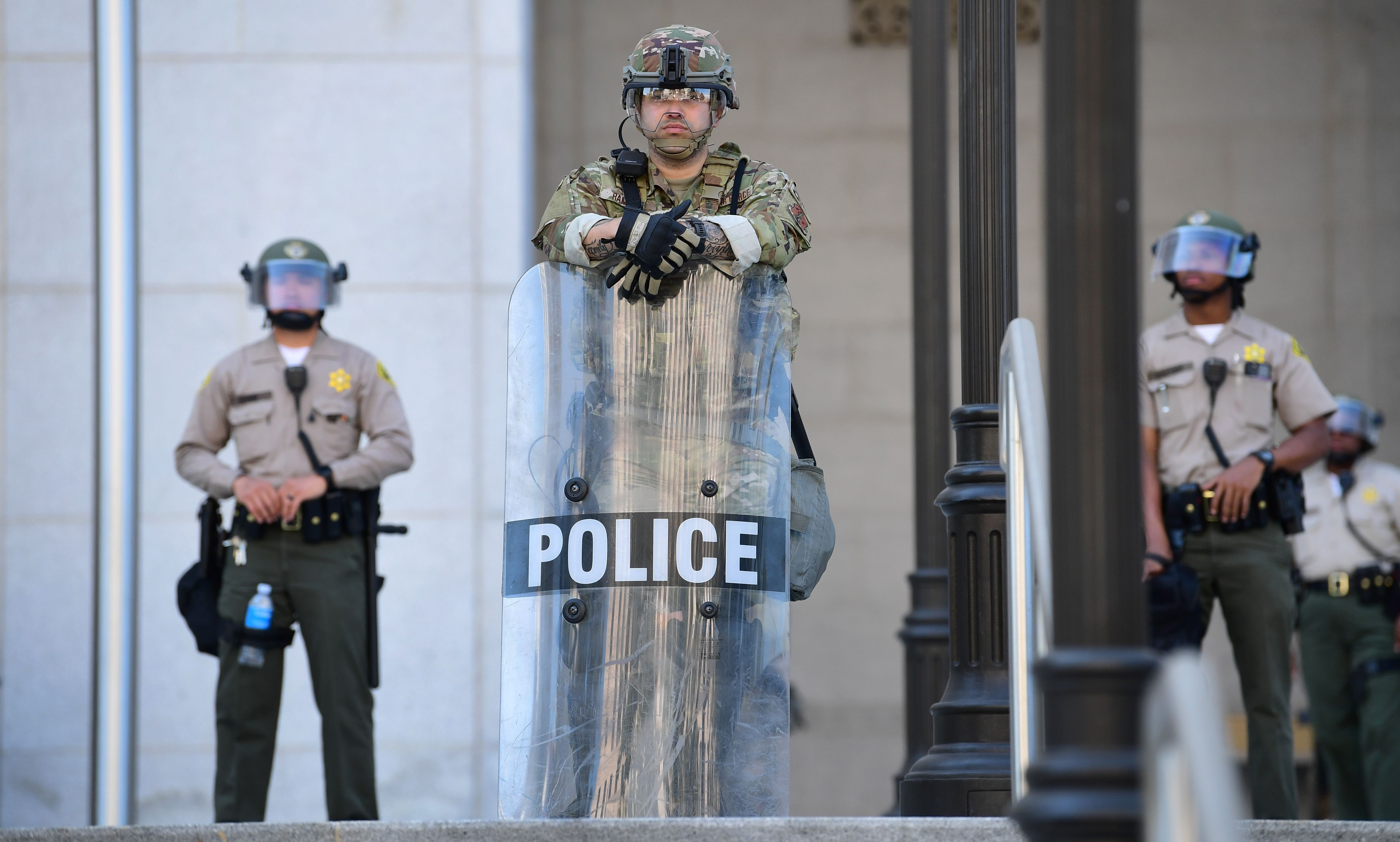 Law enforcement personnel in riot gear face protesters in Los Angeles, California on June 3, 2020 where people gathered to protest the death of George Floyd under police custody. - Derek Chauvin, the white Minneapolis police officer who kneeled on the neck of George Floyd, a black man who later died, will now be charged with second-degree murder, and his three colleagues will also face charges, court documents revealed on June 3. The May 25 death of George Floyd -- who had been accused of trying to buy cigarettes with a counterfeit bill -- has ignited protests across the United States over systemic racism and police brutality. (Photo by FREDERIC J. BROWN/AFP via Getty Images)