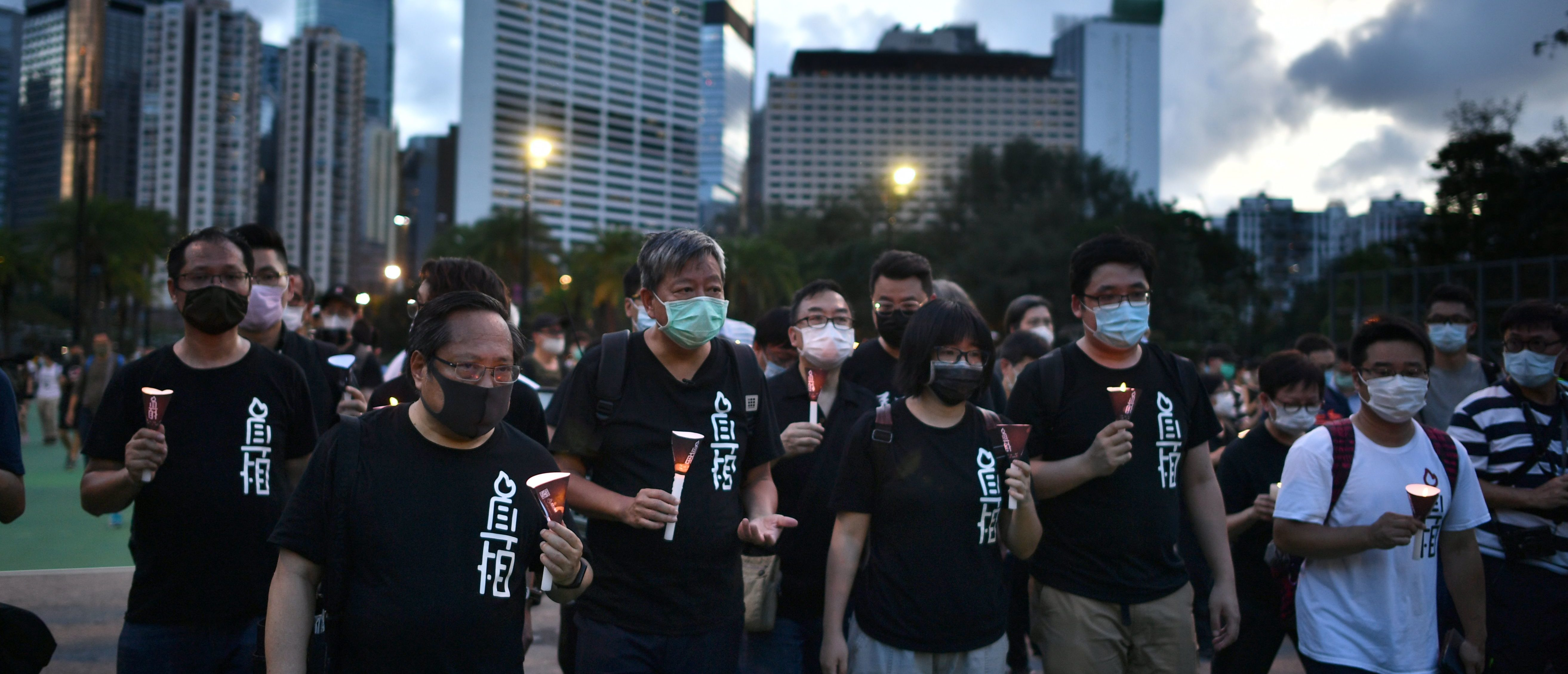 Chairman of the Alliance in Support of Patriotic Democratic Movements of China and former Legislative Council member, Lee Cheuk-yan (3rd L), leads a candlelit remembrance with other activists after crossing downed barricades into Victoria Park in Hong Kong on June 4, 2020, after the annual vigil that traditionally takes place in the park to mark the 1989 Tiananmen Square crackdown was banned on public health grounds because of the COVID-19 coronavirus pandemic. (Photo by Anthony WALLACE / AFP) (Photo by ANTHONY WALLACE/AFP via Getty Images)