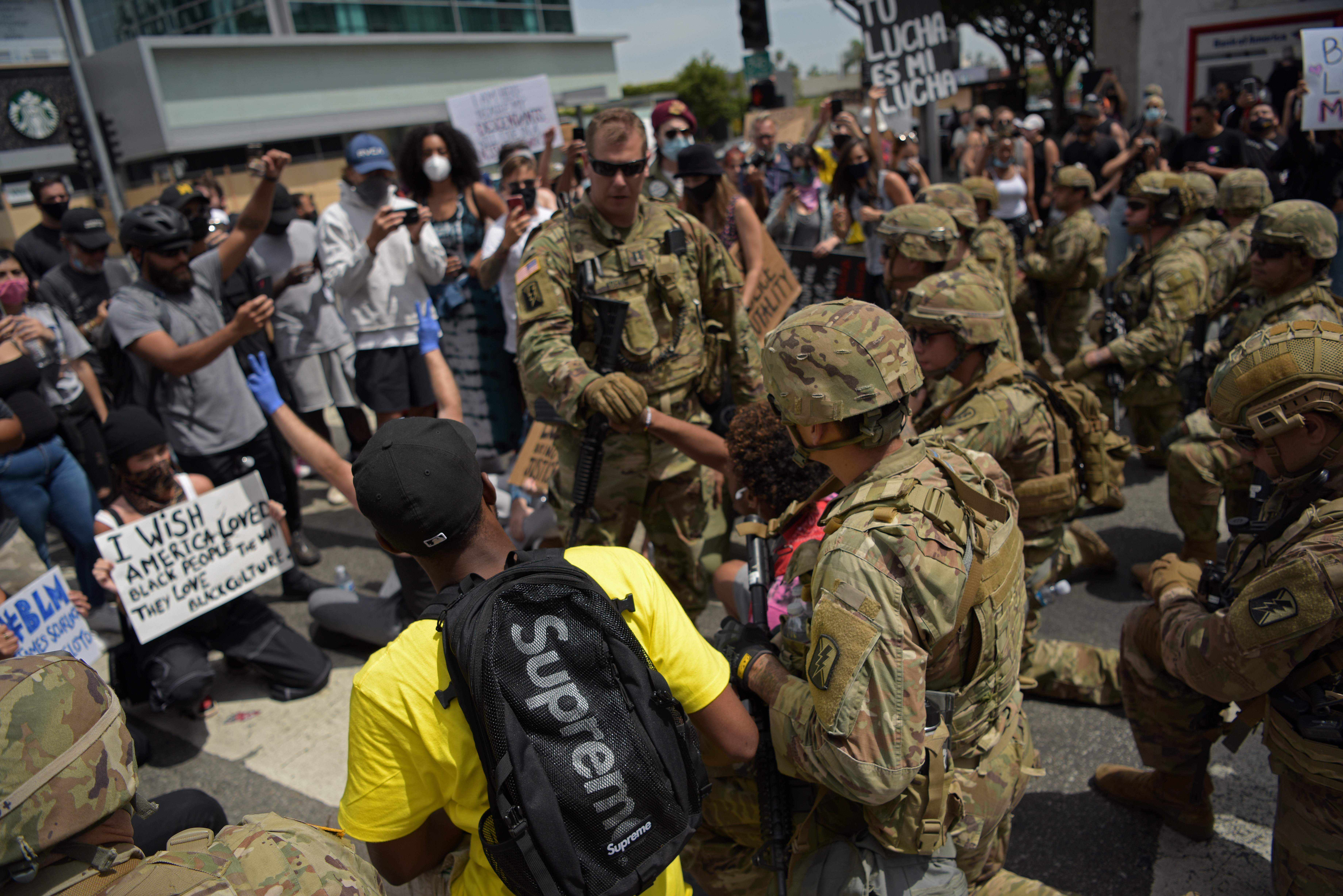 Protesters and members of the Army National Guard kneel together during a demonstration over the death of George Floyd in Los Angeles on June 2, 2020. (AGUSTIN PAULLIER/AFP via Getty Images)