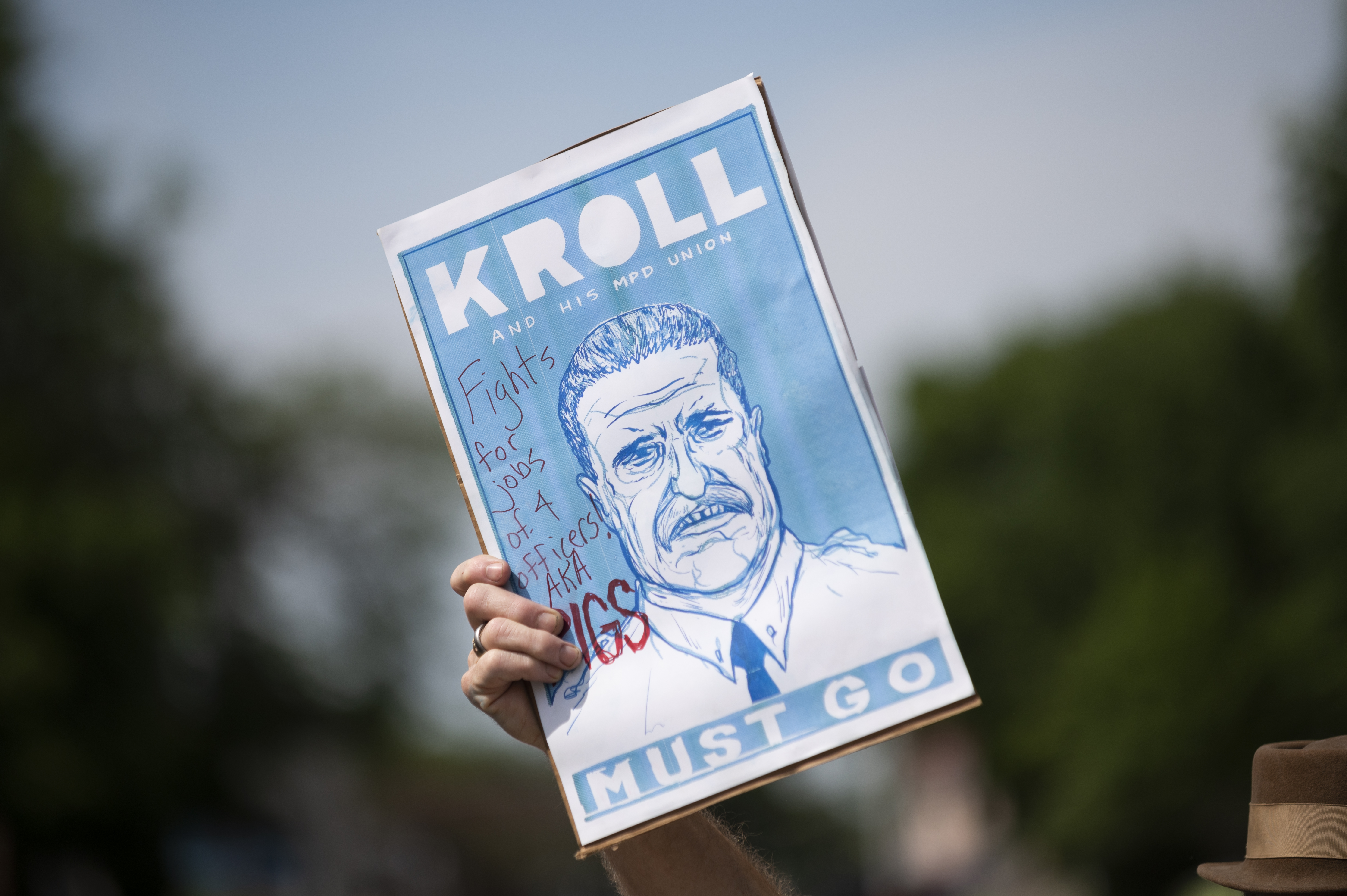"""A man holds up a sign reading """"Kroll Must Go"""" during a march calling for the city to defund the Minneapolis Police Department on June 6, 2020 in Minneapolis, Minnesota. There have been calls for Minneapolis Police Union chief Bob Kroll to resign in the wake of the killing of George Floyd on May 25 by MPD officers. (Photo by Stephen Maturen/Getty Images)"""