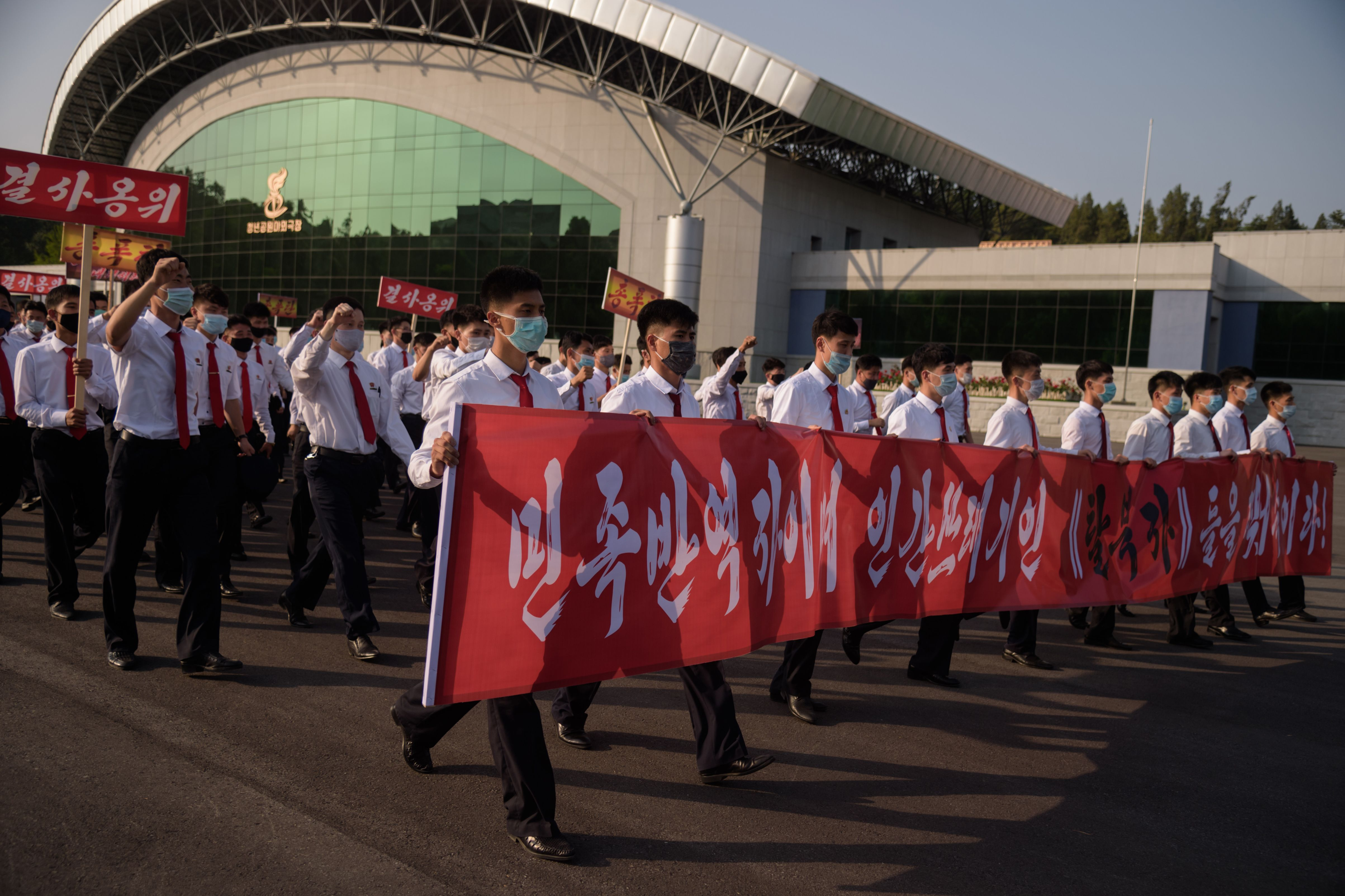"""North Korean students take part in a rally holding a banner reading: """"Tear up the 'defectors from the north' who are the betrayers of the nation and human scums!"""" as they march from the Pyongyang Youth Park Open-Air Theatre to Kim Il Sung Square in Pyongyang on June 8, 2020. (Photo by KIM WON JIN/AFP via Getty Images)"""