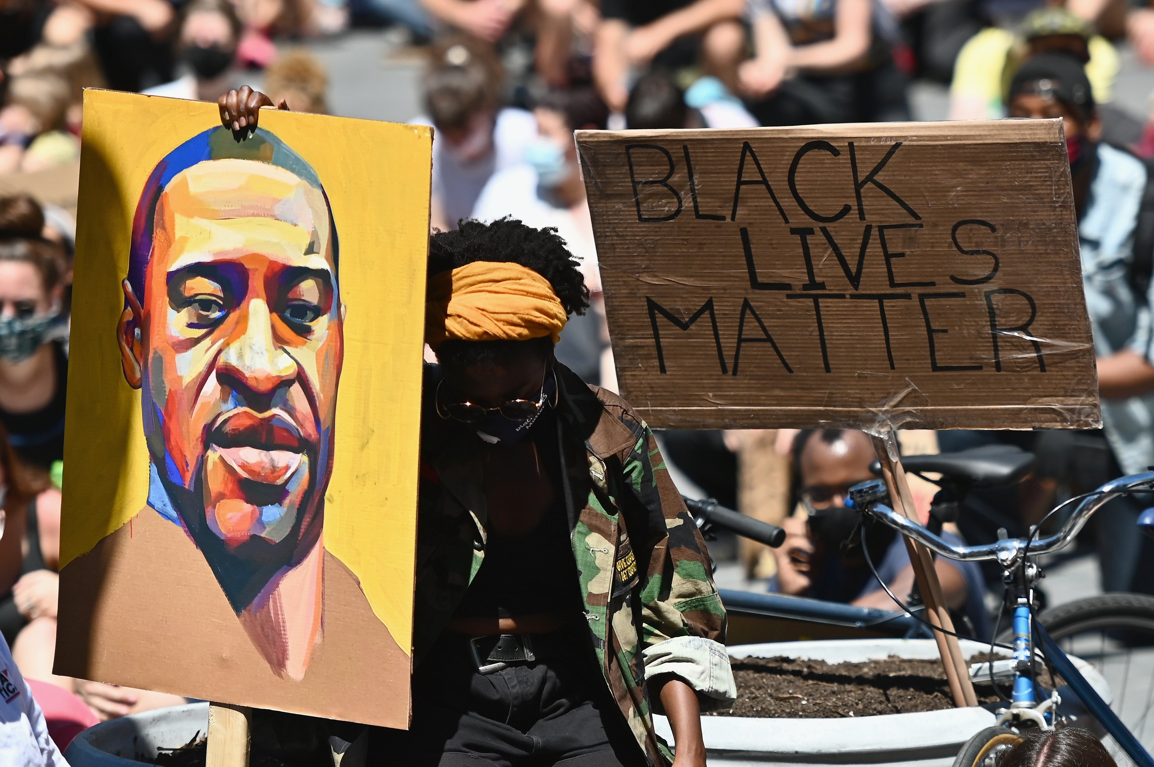 """TOPSHOT - Protesters hold up signs during a """"Black Lives Matter"""" protest in front of Borough Hall on June 8, 2020 in New York City. - On May 25, 2020, Floyd, a 46-year-old black man suspected of passing a counterfeit $20 bill, died in Minneapolis after Derek Chauvin, a white police officer, pressed his knee to Floyd's neck for almost nine minutes. (Photo by ANGELA WEISS/AFP via Getty Images)"""