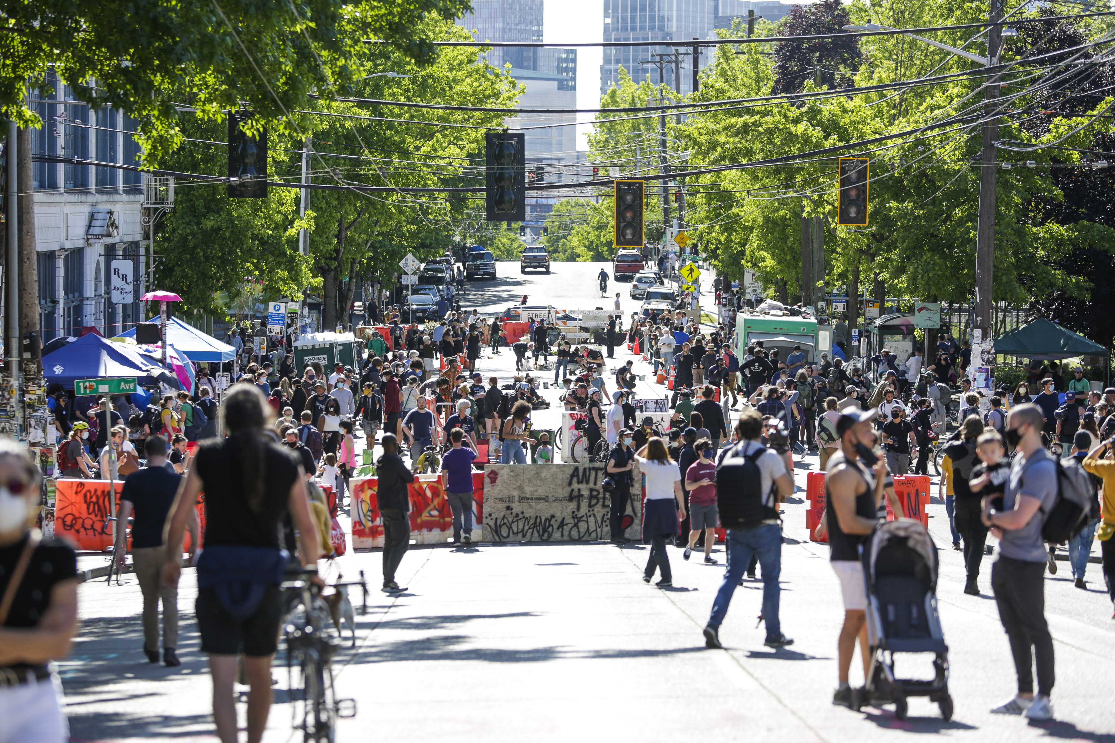 People walk around the newly created Capitol Hill Autonomous Zone (CHAZ), in Seattle, Washington on June 11, 2020. - The area surrounding the East Precinct building has come to be known as the CHAZ, Capitol Hill Autonomous Zone. Volunteer medics are available to tend to medical needs, alongside tents with medical supplies, gourmet food donated form local restaurants, fruit, snacks, water bottles free for whomever needed them. (Photo by JASON REDMOND/AFP via Getty Images)
