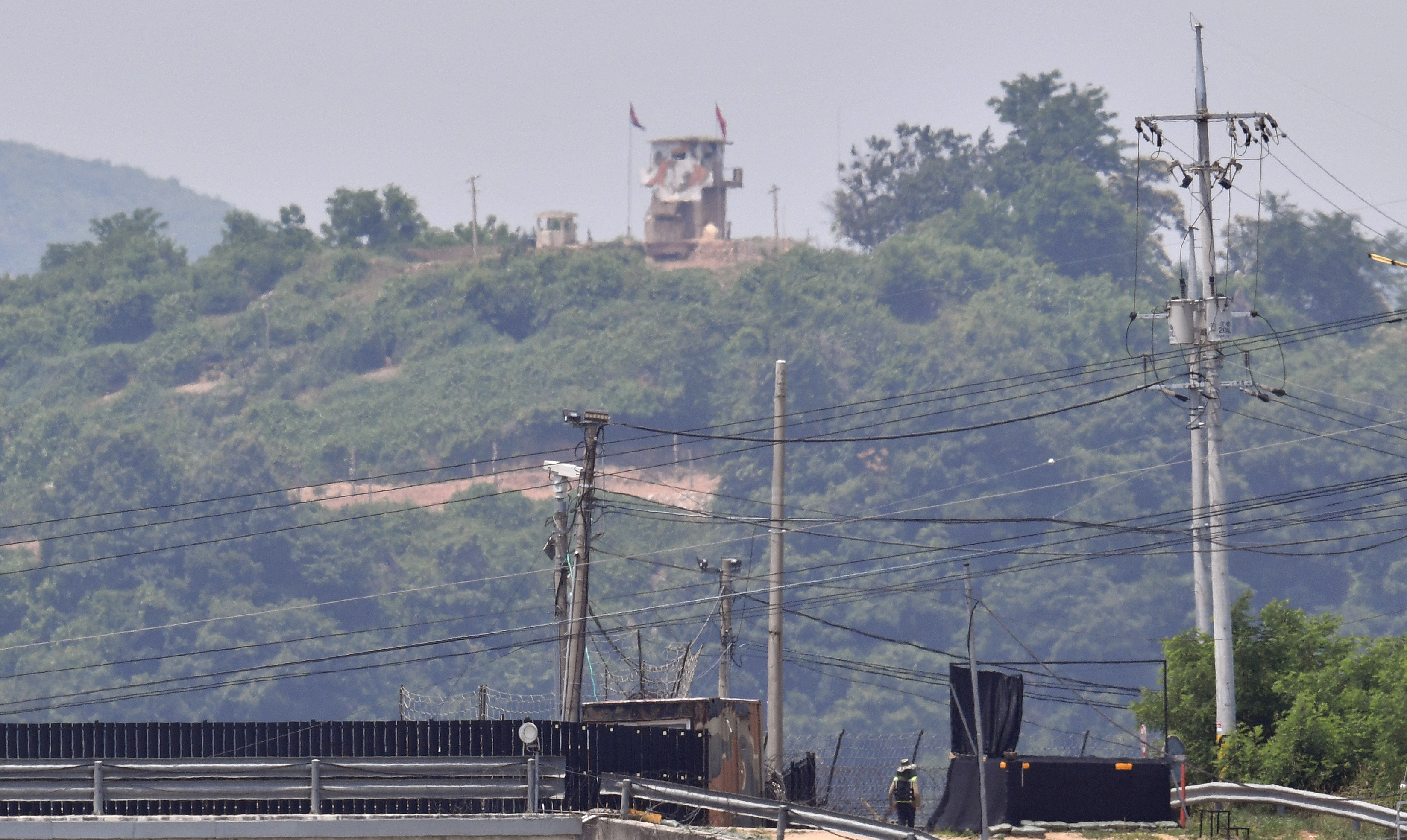 A North Korean guard post (top) is seen over a South Korean military fence (bottom) from the border city of Paju on June 16, 2020. (Photo by JUNG YEON-JE/AFP via Getty Images)
