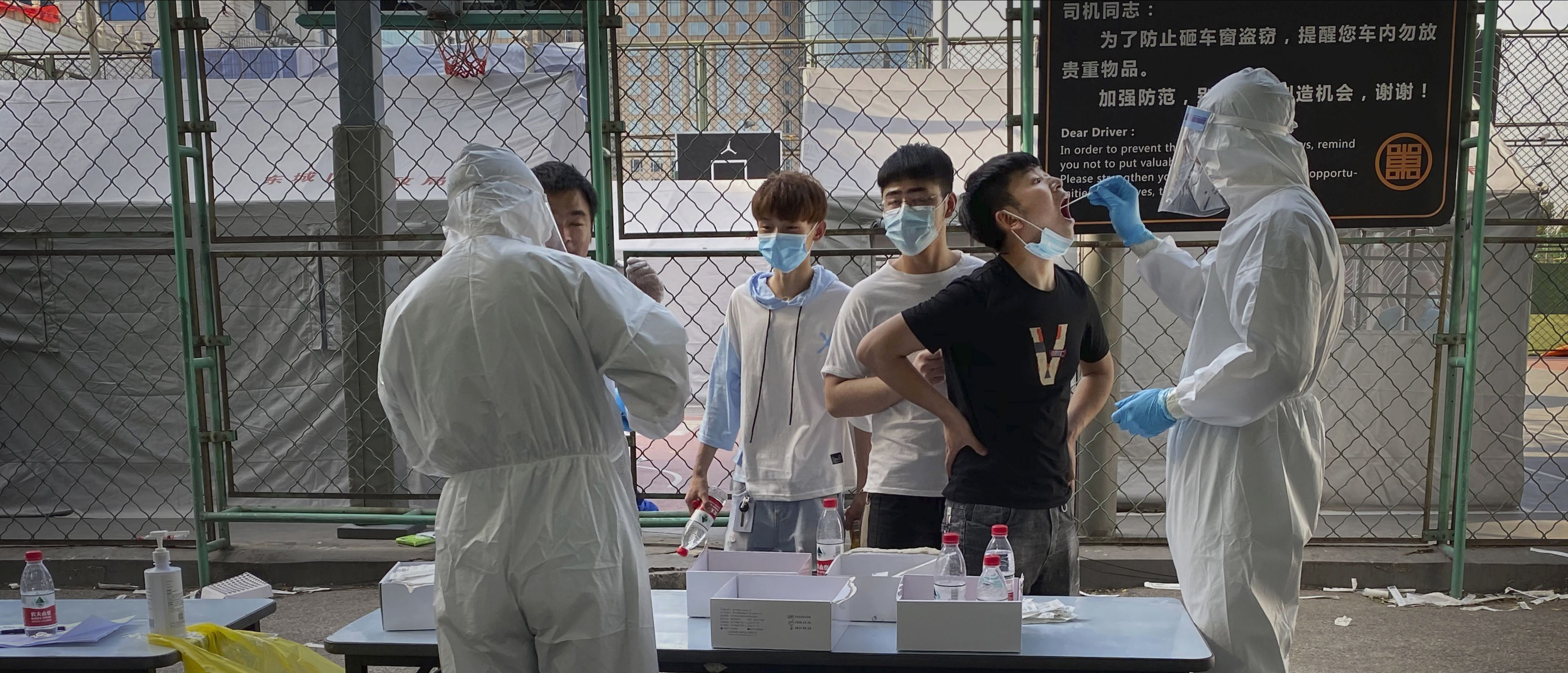 BEIJING, CHINA - JUNE 16:(eds note: photo taken with mobile phone) A Chinese epidemic control worker wears a protective suit and mask while performing a nucleic acid test for COVID-19 on a man who has had contact with the Xinfadi Wholesale Market or someone who has, at a testing center on June 16, 2020 in Beijing, China. Authorities are trying to contain the outbreak linked to the Xinfadi wholesale food market, Beijing's biggest supplier of produce and meat. Several neighborhoods have been locked down and at least two other food markets were closed, as tens of thousands of people are being urged to get tested for COVID-19 at sites set up around the city. The outbreak has triggered fears of a second wave of infection after 56 straight days with no domestically transmitted cases in the capital. More than 8,000 vendors and staff at Xinfadi have already been tested, according to city officials, who are using contact tracing to reach an estimated 200,000 people who have visited the market since May 30. (Photo by Kevin Frayer/Getty Images)