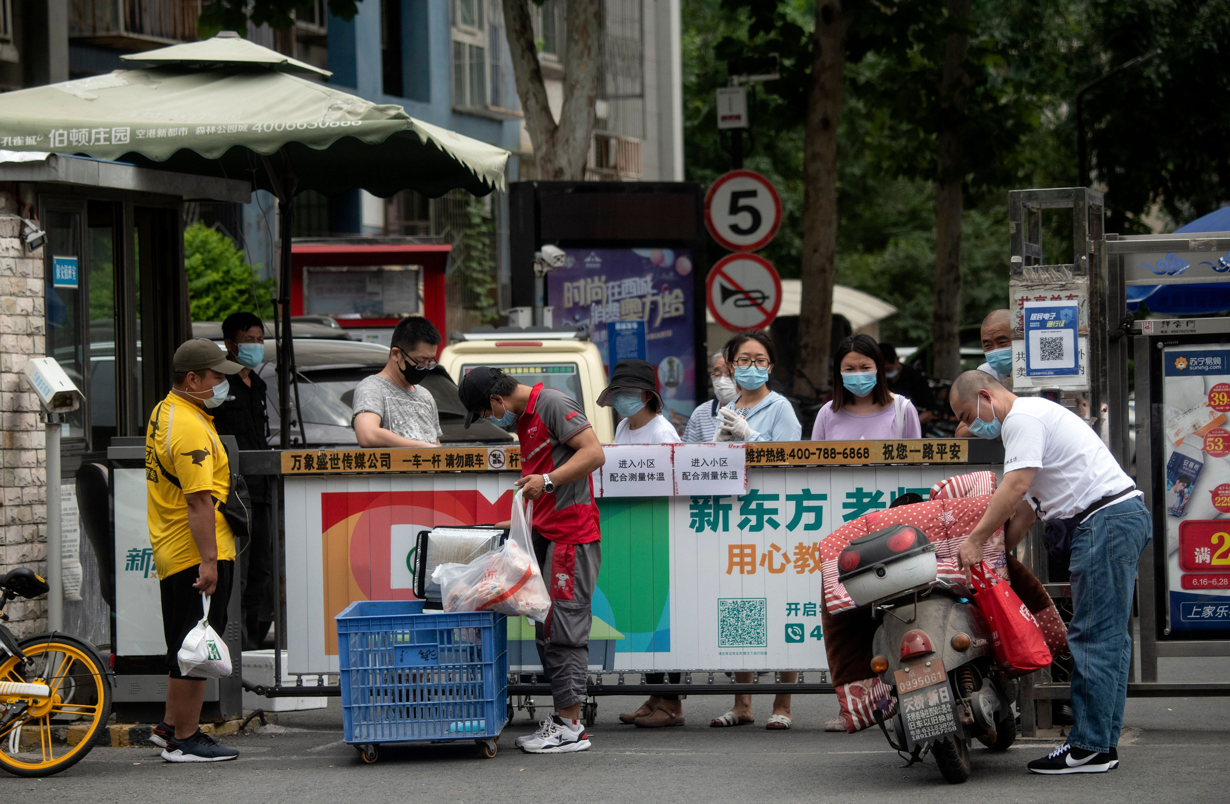 People wearing face masks wait for the delivery of goods they ordered online in a residential area in Xicheng district which is under lockdown after a new COVID-19 coronavirus outbreak near the closed Xinfadi Market in Beijing on June 17, 2020. (Photo by NOEL CELIS/AFP via Getty Images)