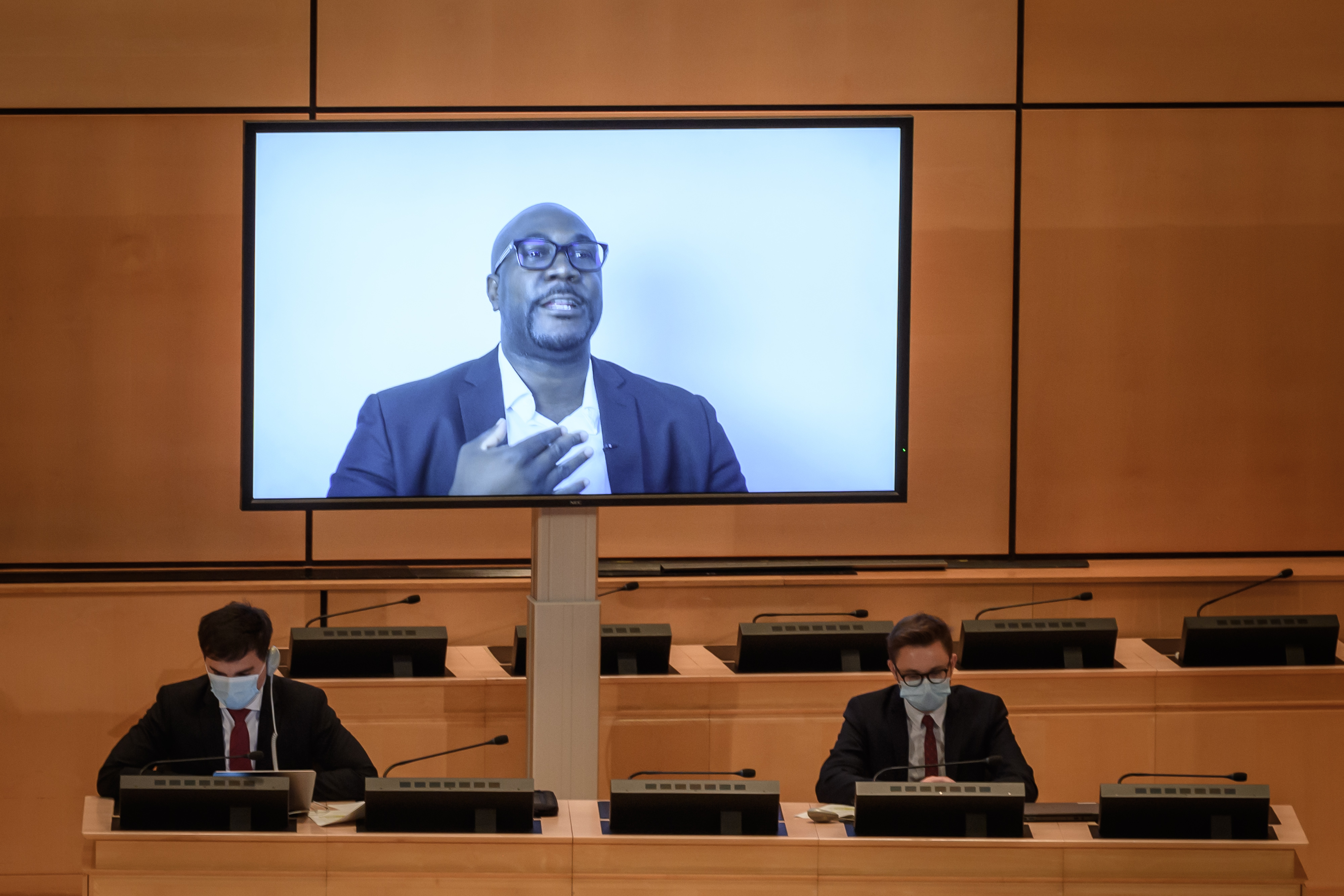 """George Floyd's brother Philonise is seen on a TV screen during his speech at the opening of an urgent debate on """"systemic racism"""" in the United States and beyond at the Human Rights Council on June 17, 2020 in Geneva. (Photo by FABRICE COFFRINI/AFP via Getty Images)"""
