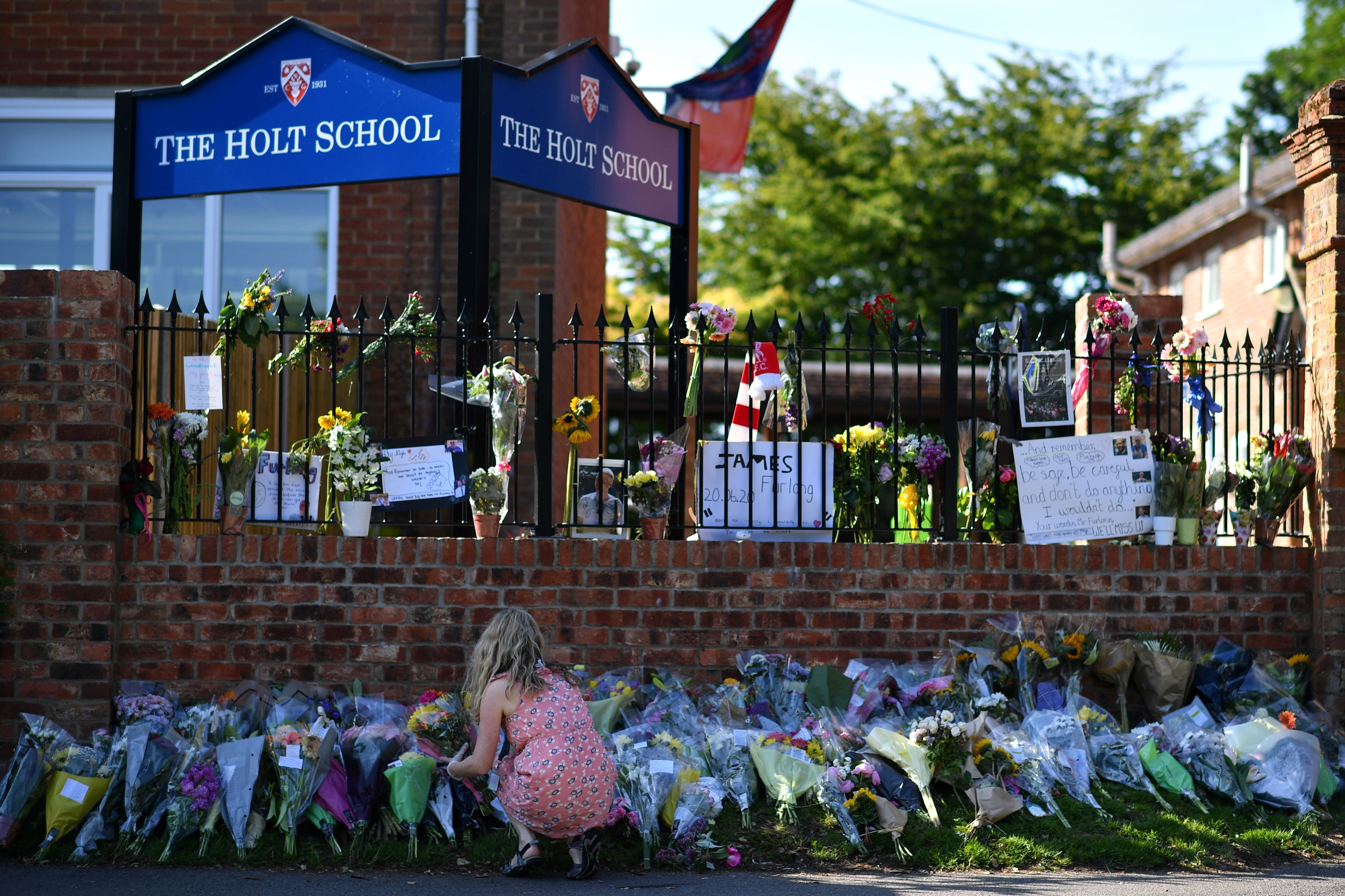 A teacher rearranges a floral tribute outside The Holt School in Wokingham on June 23, 2020 in memory of teacher James Furlong who was a victim in the knife attack in Reading which killed three people. (Photo by BEN STANSALL/AFP via Getty Images)