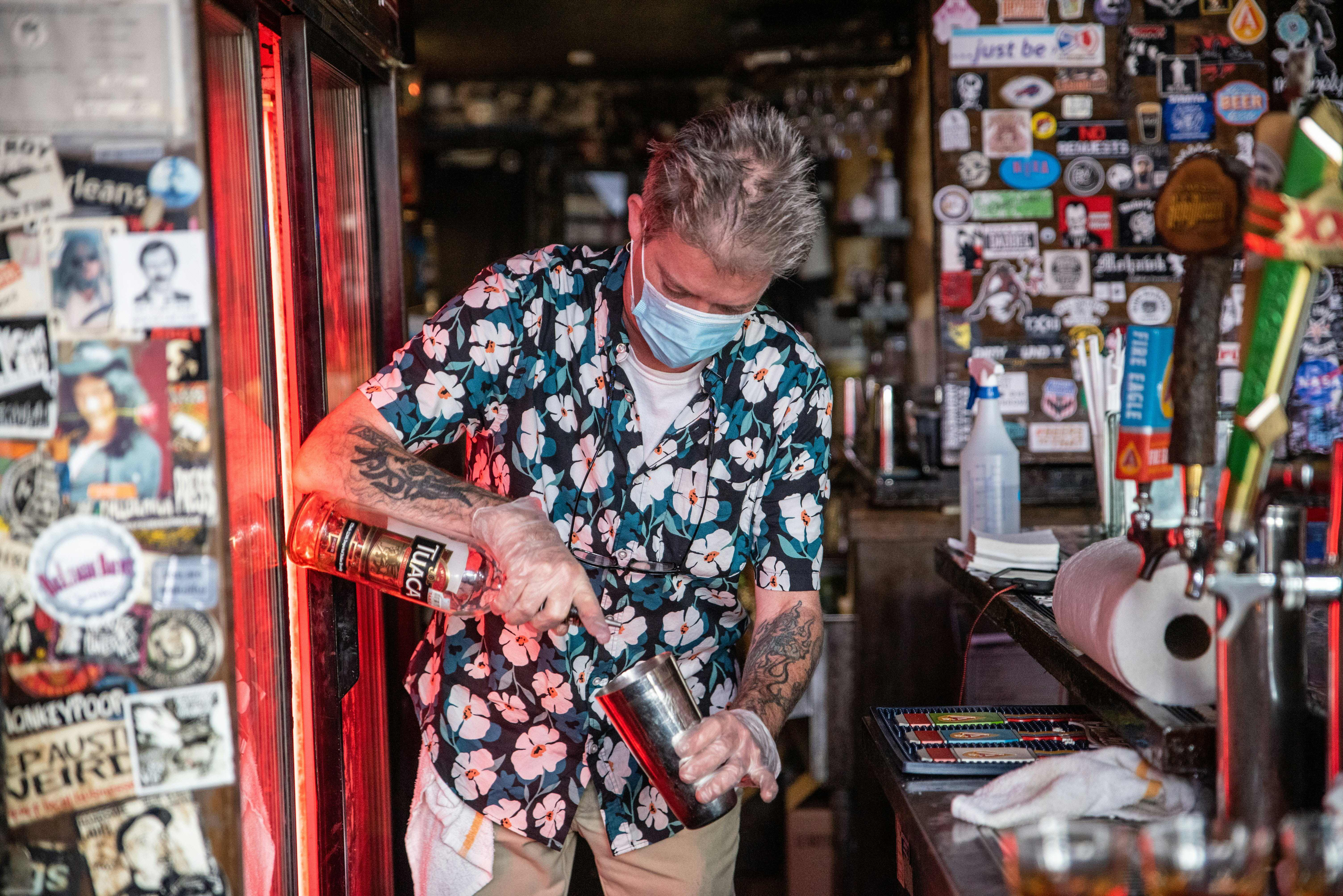 A bartender wearing a facemask makes a drink at a restaurant in Austin, Texas, June 26, 2020. - Texas Governor Greg Abbott ordered bars to be closed by noon on June 26 and for restaurants to be reduced to 50% occupancy. Coronavirus cases in Texas have spiked in recent weeks after being one of the first states to begin reopening. (Photo by SERGIO FLORES/AFP via Getty Images)