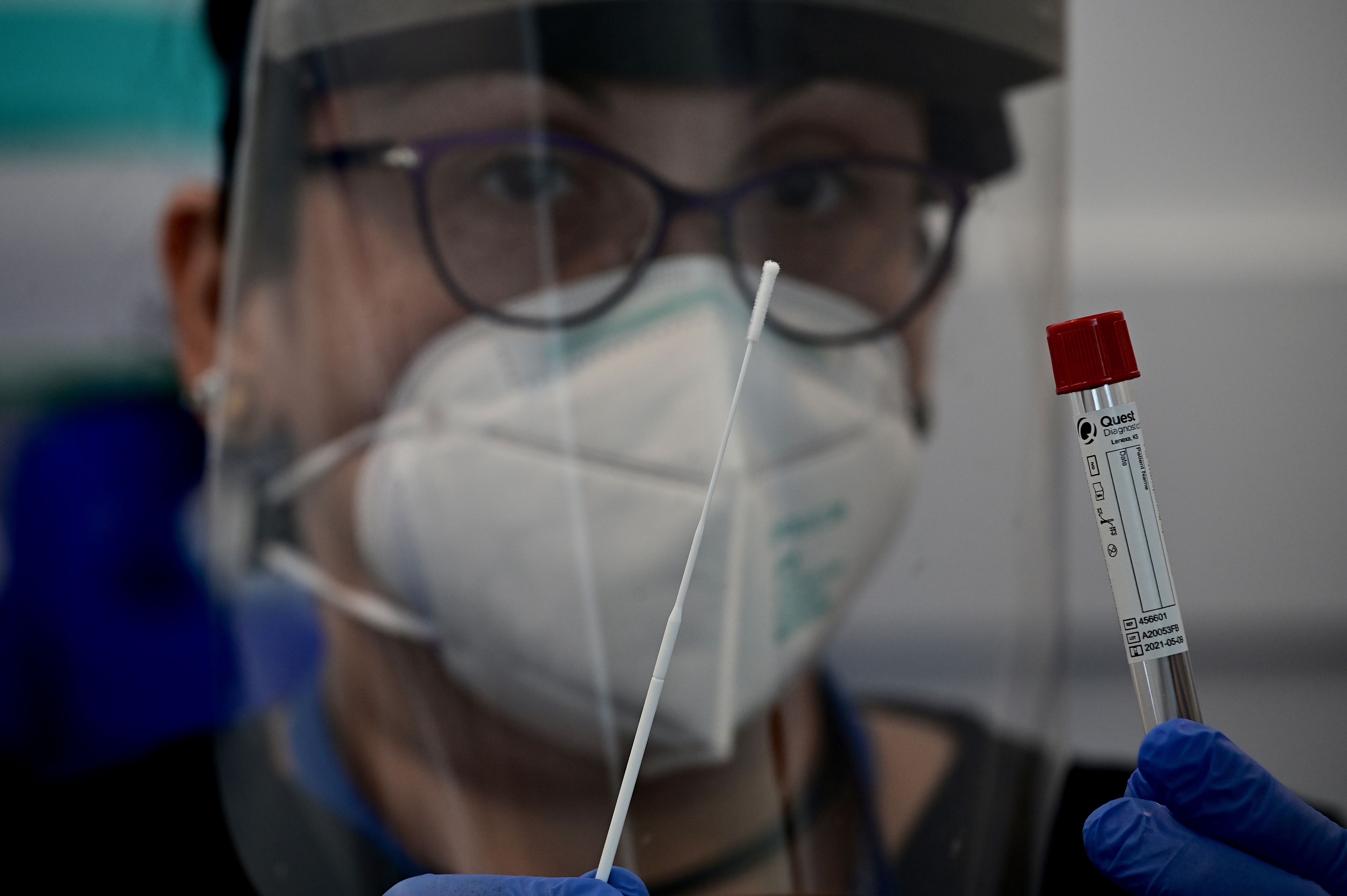 Nurse Christina poses with a nasal swab at JFK International Airports Terminal 4 XpresCheck the first airport-based covid-19 testing facility in the US on June 29, 2020 in New York City. - The pilot program will be available to all airport employees and offers Covid and antibody testing. (Photo by JOHANNES EISELE/AFP via Getty Images)