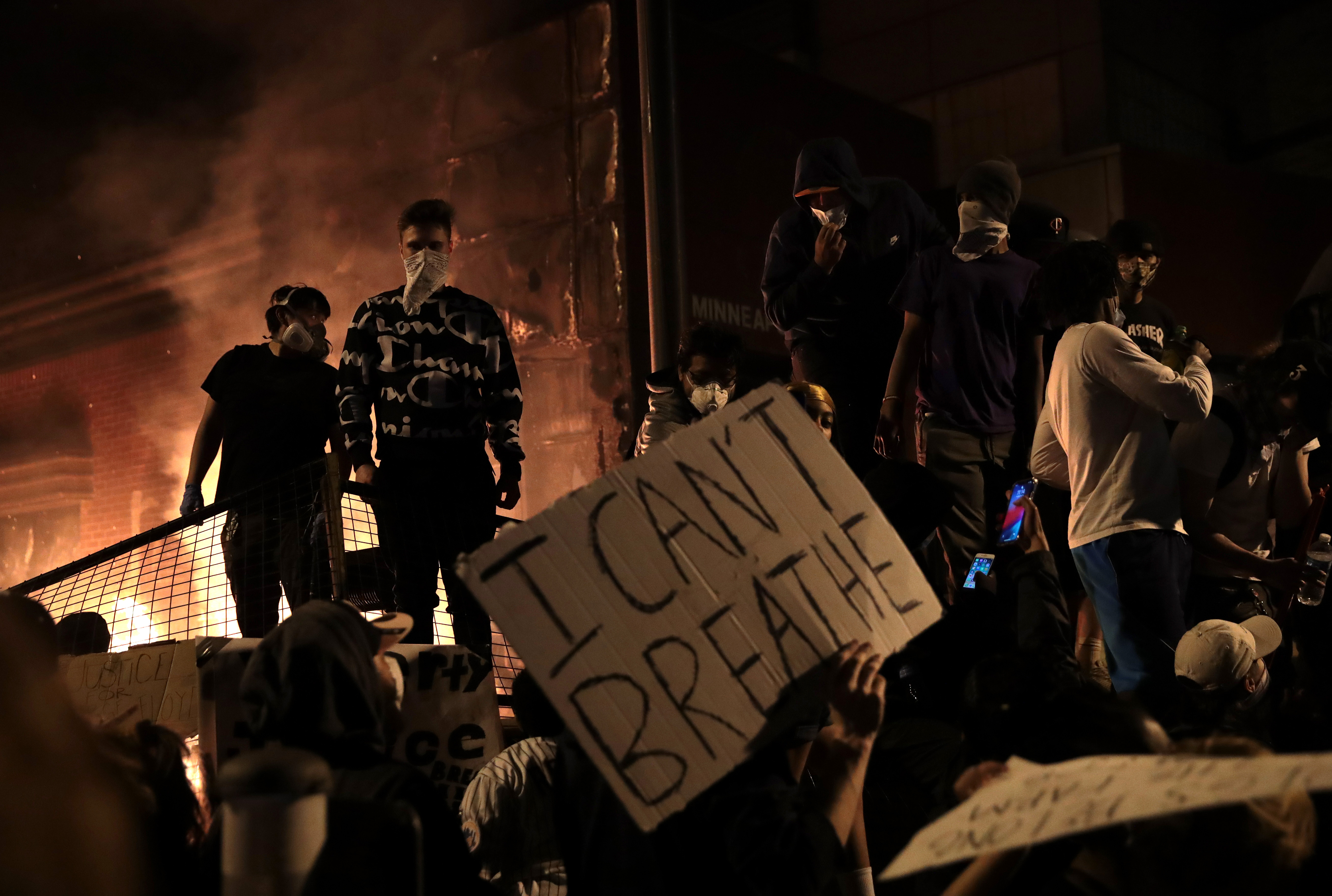 "Protesters stand in front of the 3rd precinct police building as it burns during a protest on May 28, 2020 in Minneapolis, Minnesota. Today marks the third day of ongoing protests after the police killing of George Floyd. Four Minneapolis police officers have been fired after a video taken by a bystander was posted on social media showing Floyd's neck being pinned to the ground by an officer as he repeatedly said, ""I can't breathe"". Floyd was later pronounced dead while in police custody after being transported to Hennepin County Medical Center. (Photo by Scott Olson/Getty Images)"