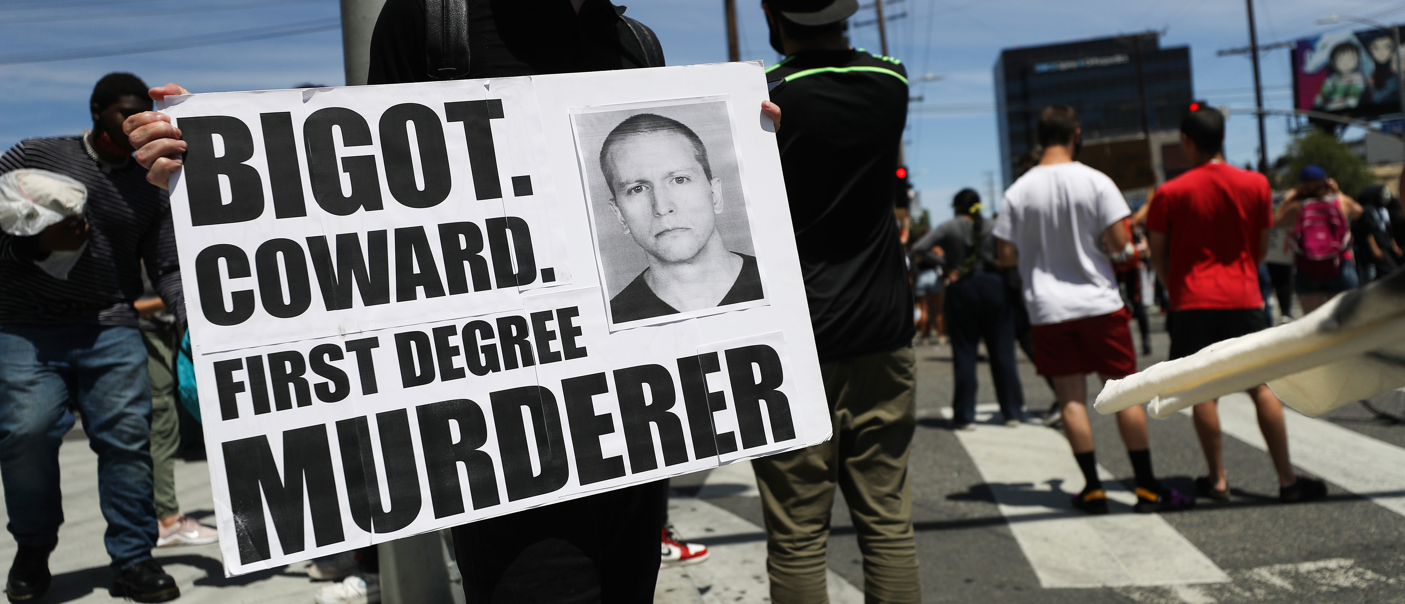 LOS ANGELES, CALIFORNIA - MAY 30: A protester holds a sign with a photo of former Minneapolis police officer Derek Chauvin during demonstrations following the death of George Floyd on May 30, 2020 in Los Angeles, California. Chauvin was taken into custody for Floyd's death. Chauvin has been accused of kneeling on Floyd's neck as he pleaded with him about not being able to breathe. Floyd was pronounced dead a short while later. Chauvin and 3 other officers, who were involved in the arrest, were fired from the police department after a video of the arrest was circulated. (Photo by Mario Tama/Getty Images)