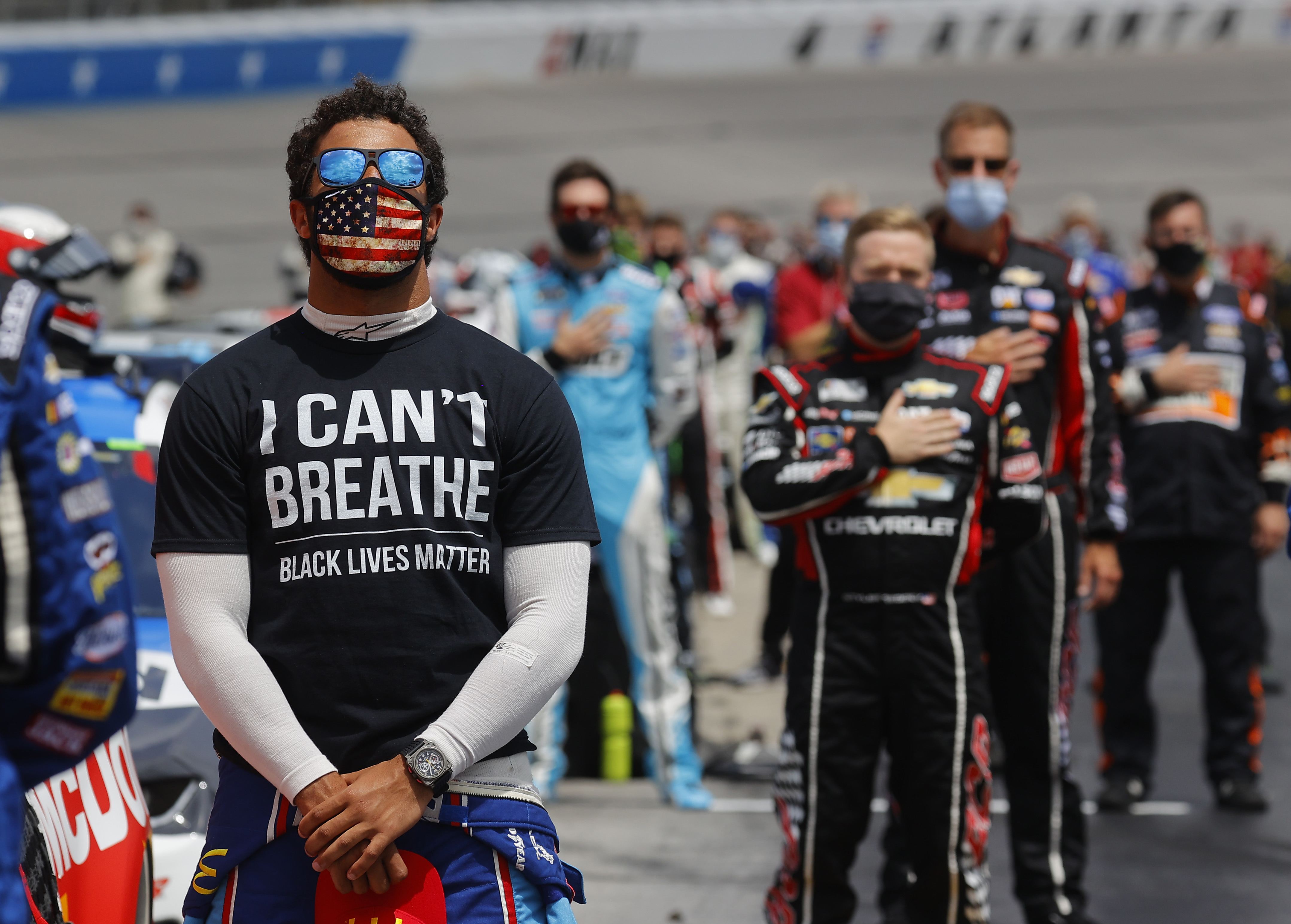 "Bubba Wallace, driver of the #43 McDonald's Chevrolet, wears a ""I Can't Breathe - Black Lives Matter"" T-shirt under his fire suit in solidarity with protesters around the world taking to the streets after the death of George Floyd on May 25 while in the custody of Minneapolis, Minnesota police, stands during the national anthem prior to the NASCAR Cup Series Folds of Honor QuikTrip 500 at Atlanta Motor Speedway on June 07, 2020 in Hampton, Georgia. (Photo by Chris Graythen/Getty Images)"