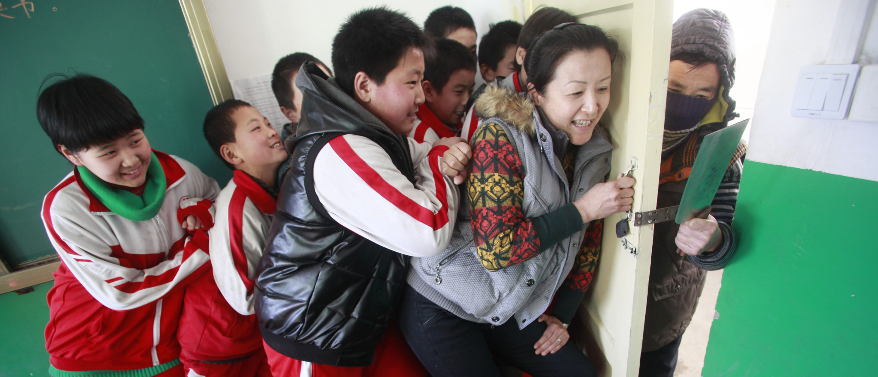 This picture taken on December 18, 2012 shows students and a teacher (2nd R) trying to stop an attacker (R) during a drill on a mock attack at a primary school in Jinan, in eastern China's Shandong province. The drill came four days after a knife-wielding attacker stabbed 22 students at a primary school in the central Chinese province of Henan on December 14 in the latest in a series of assaults. China has seen several violent attacks against children over the past two years, including a spate of five incidents in 2010 which killed 15 children and two adults and wounded more than 80. CHINA OUT AFP PHOTO (Photo credit should read STR/AFP via Getty Images)