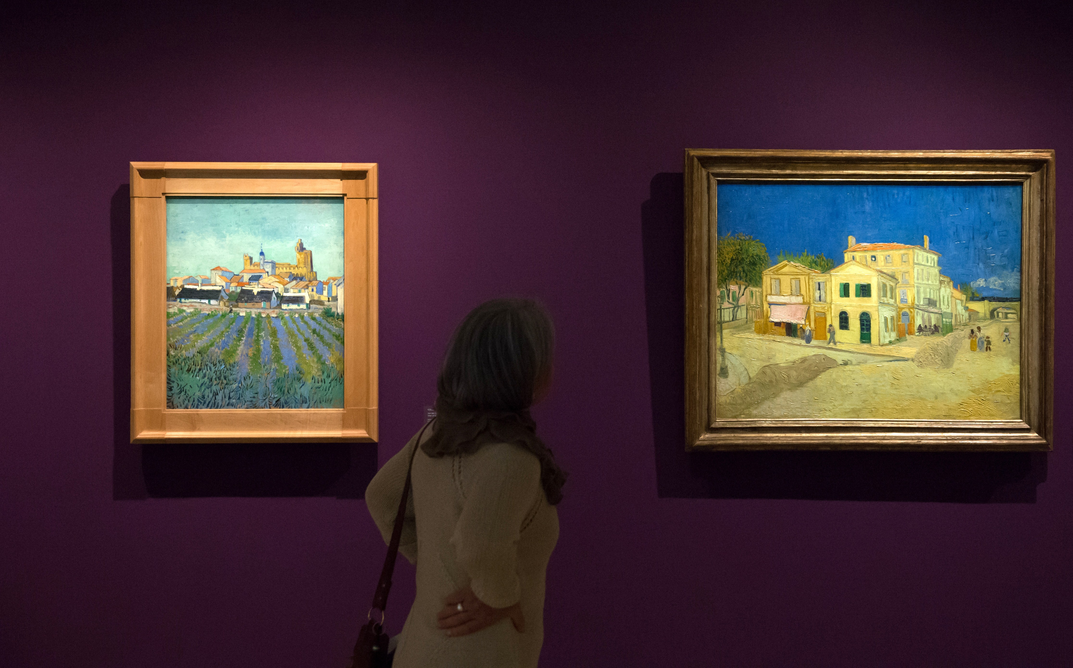 A woman looks at paintings entitled 'View of the Saintes-Maries-de-la-Mer' (1888) and 'La maison jaune' (The yellow house- 1888) by Dutch painter Vincent Willem van Gogh during the press preview of the exhibition 'Van Gogh live !' as part of the opening of the Fondation Vincent van Gogh Arles on April 3, 2014 in Arles, southern France. (BERTRAND LANGLOIS/AFP via Getty Images)