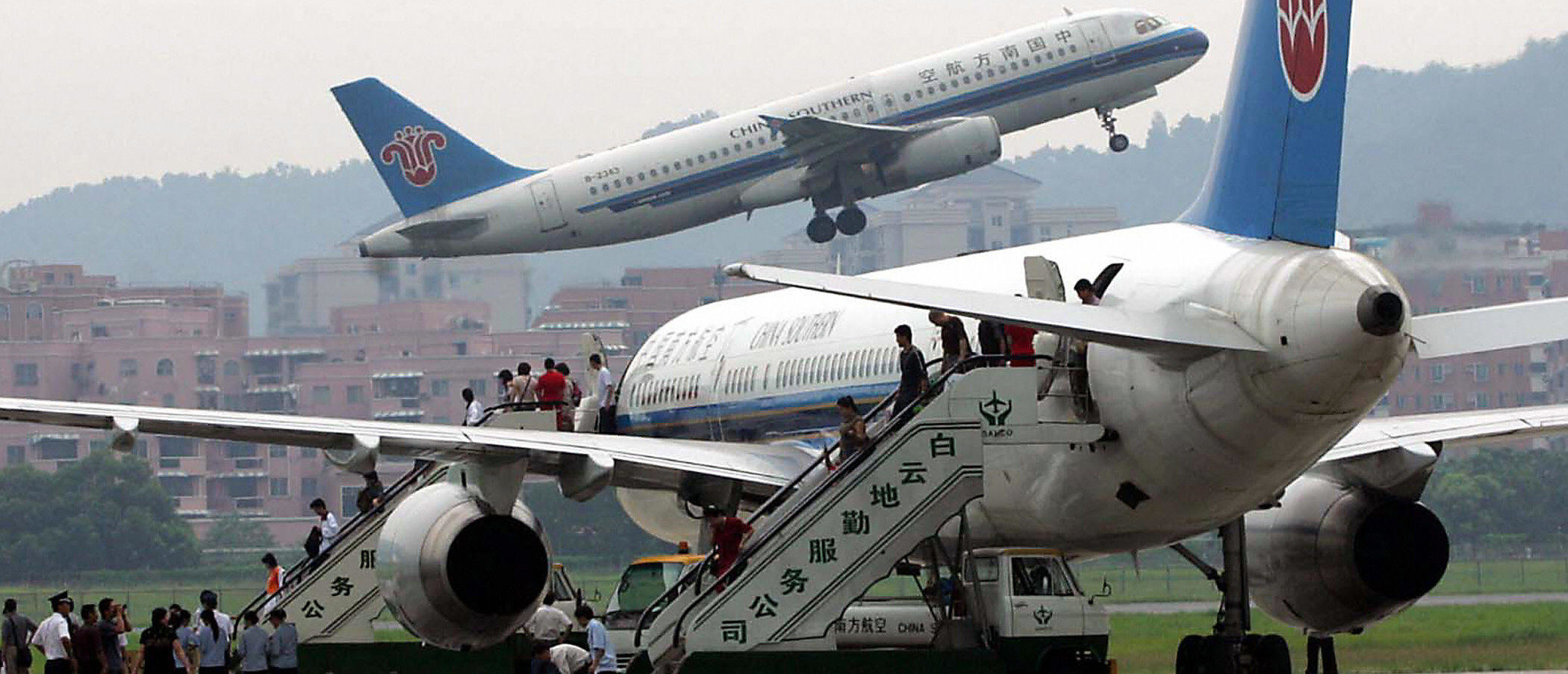 GUANGZHOU, CHINA: Passengers board the last of the China Southern airlines plane to take off from the old Baiyun airport in Guangzhou, southern China's Guangdong province 04 August 2004, prior to the opening of the new airport tomorrow. The southern Chinese city of Guangzhou opens a huge new international airport this week capable of handling 25 million passengers a year in a direct challenge to neighbouring Hong Kong's role as an Asian hub, as the first flight will take off from the 19 billion yuan (2.4 billion-dollar) state-of-the-art Baiyun International Airport on Thursday, making China's third largest city a major player in Asia's aviation market. AFP PHOTO (Photo credit should read STR/AFP via Getty Images)