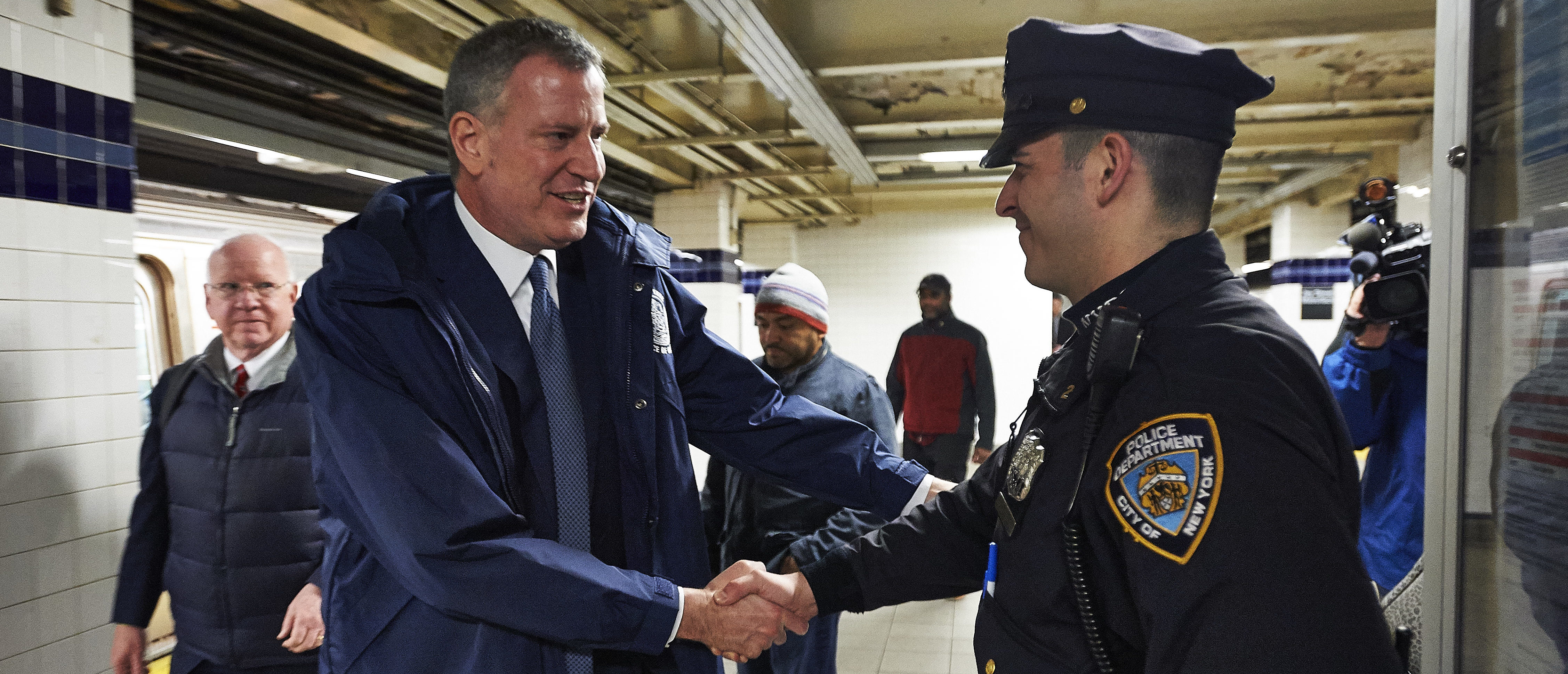 NEW YORK, NY - MARCH 3: New York City Mayor Bill de Blasio, left, greets a New York Police Department officer after a trip on the New York City Subway A train on March 2, 2016 in New York City. The Mayor rode the subway from City Hall to a news conference in Brooklyn. (Photo by James Keivom-Pool/Getty Images)