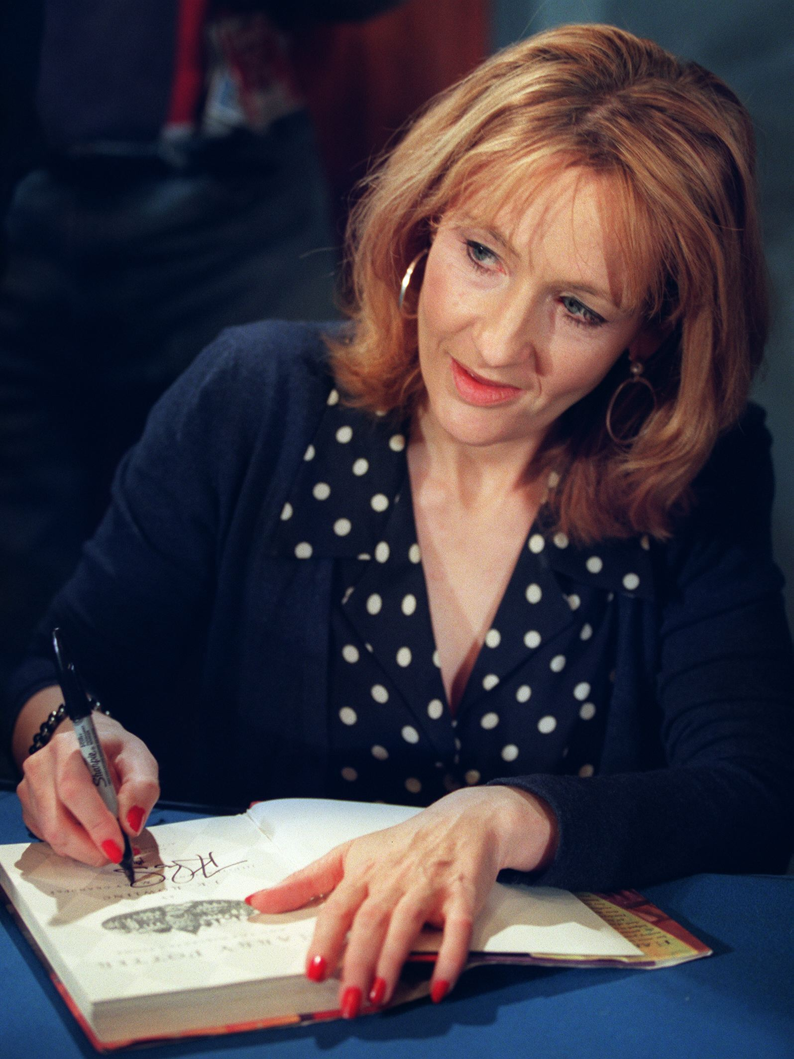 WASHINGTON, : J.K. Rowling, author of the best-selling Harry Potter children's books autographs one of her works during a book signing 20 October, 1999 in Washington, DC. Rowling's books, featuring Harry Potter a fictional orphan who attends a school for wizards, have become controversial in recent weeks as parents in a South Carolina school district seek to have the books banned for violent content. (Photo credit should read TIM SLOAN/AFP via Getty Images)
