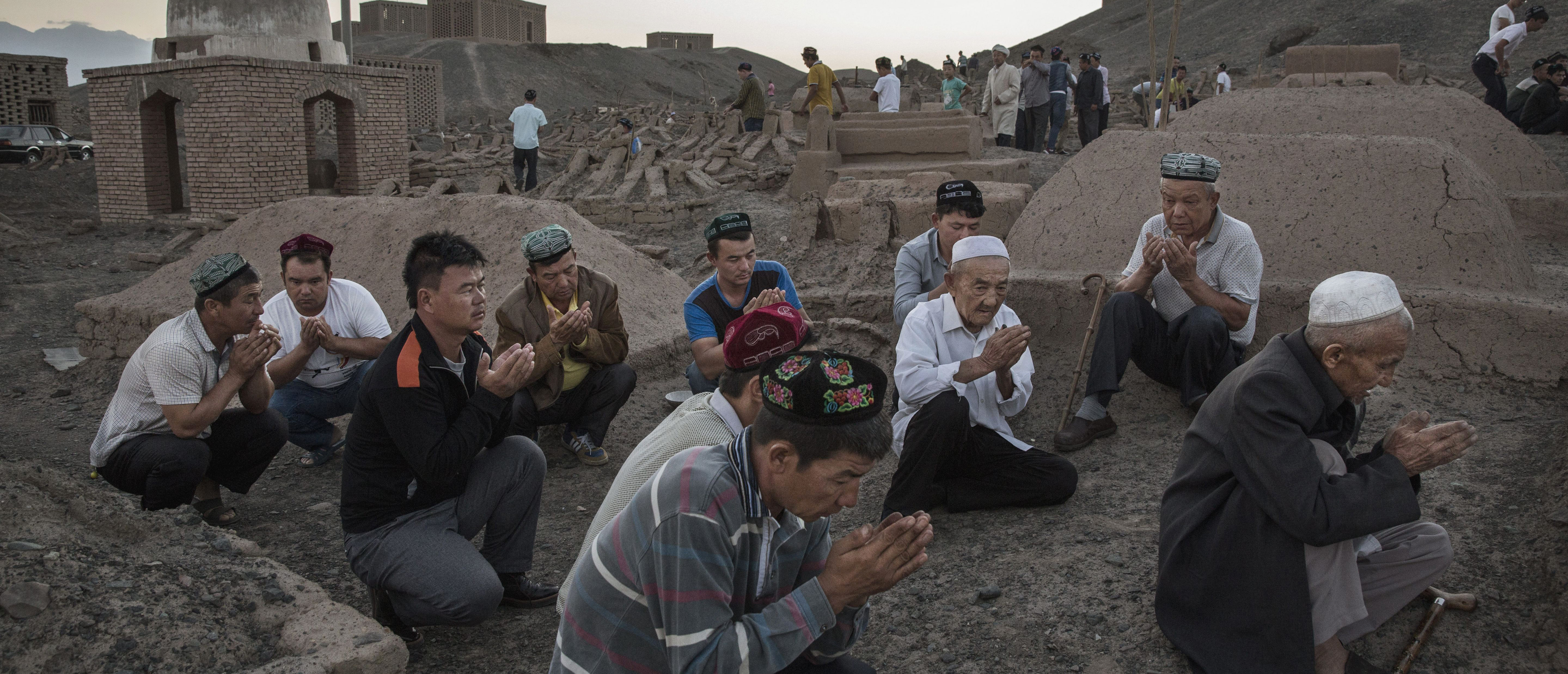 TURPAN, CHINA - SEPTEMBER 11: (CHINA OUT) Uyghur men perform prayers for ancestors at a cemetery before the Corban Festival on September 11, 2016 in Turpan County, in the far western Xinjiang province, China. The Corban festival, known to Muslims worldwide as Eid al-Adha or 'feast of the sacrifice', is celebrated by ethnic Uyghurs across Xinjiang, the far-western region of China bordering Central Asia that is home to roughly half of the country's 23 million Muslims. (Photo by Kevin Frayer/Getty Images)
