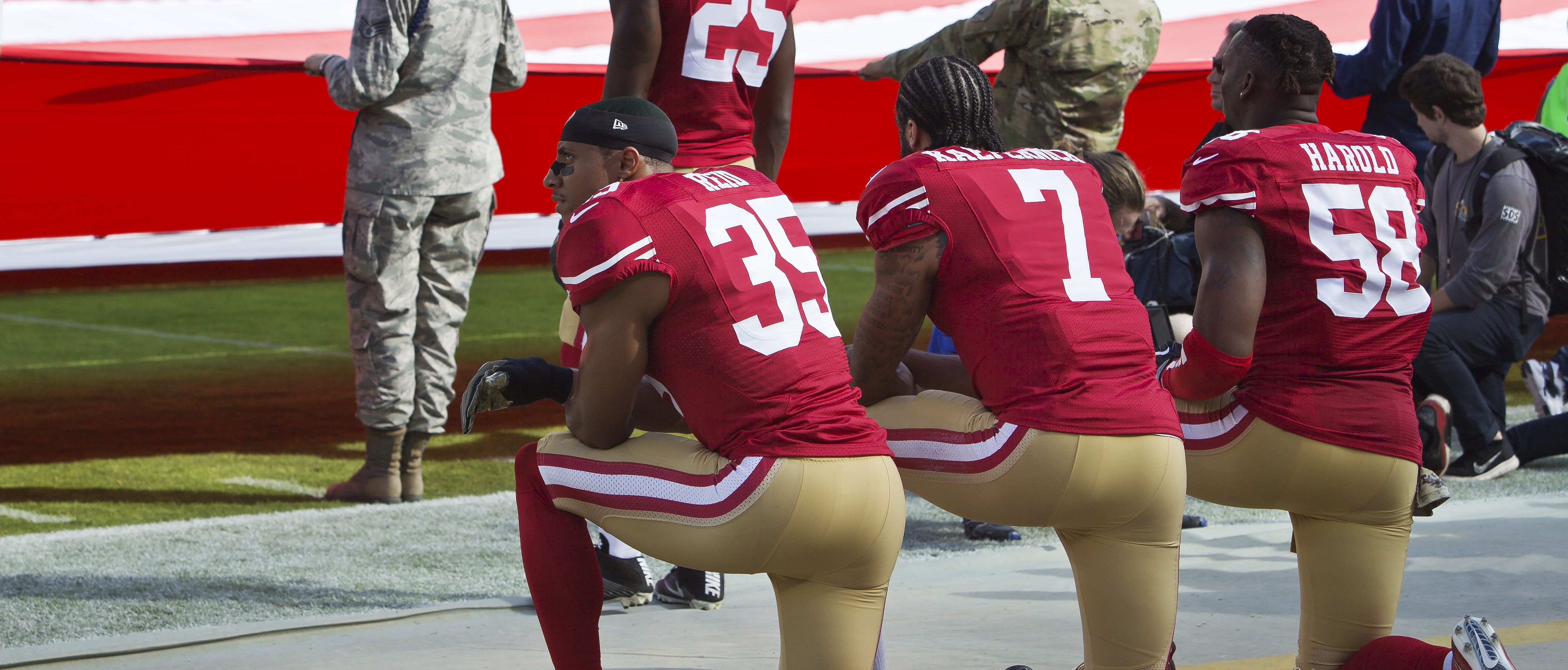SANTA CLARA, CA - NOVEMBER 6: Quarterback Colin Kaepernick #7, safety Eric Reid #35, and linebacker Eli Harold #58 of the San Francisco 49ers kneel before a game against the New Orleans Saints with the U.S. flag unfurled in honor of the armed services on November, 6 2016 at Levi's Stadium in Santa Clara, California. The Saints won 41-23. (Photo by Brian Bahr/Getty Images)