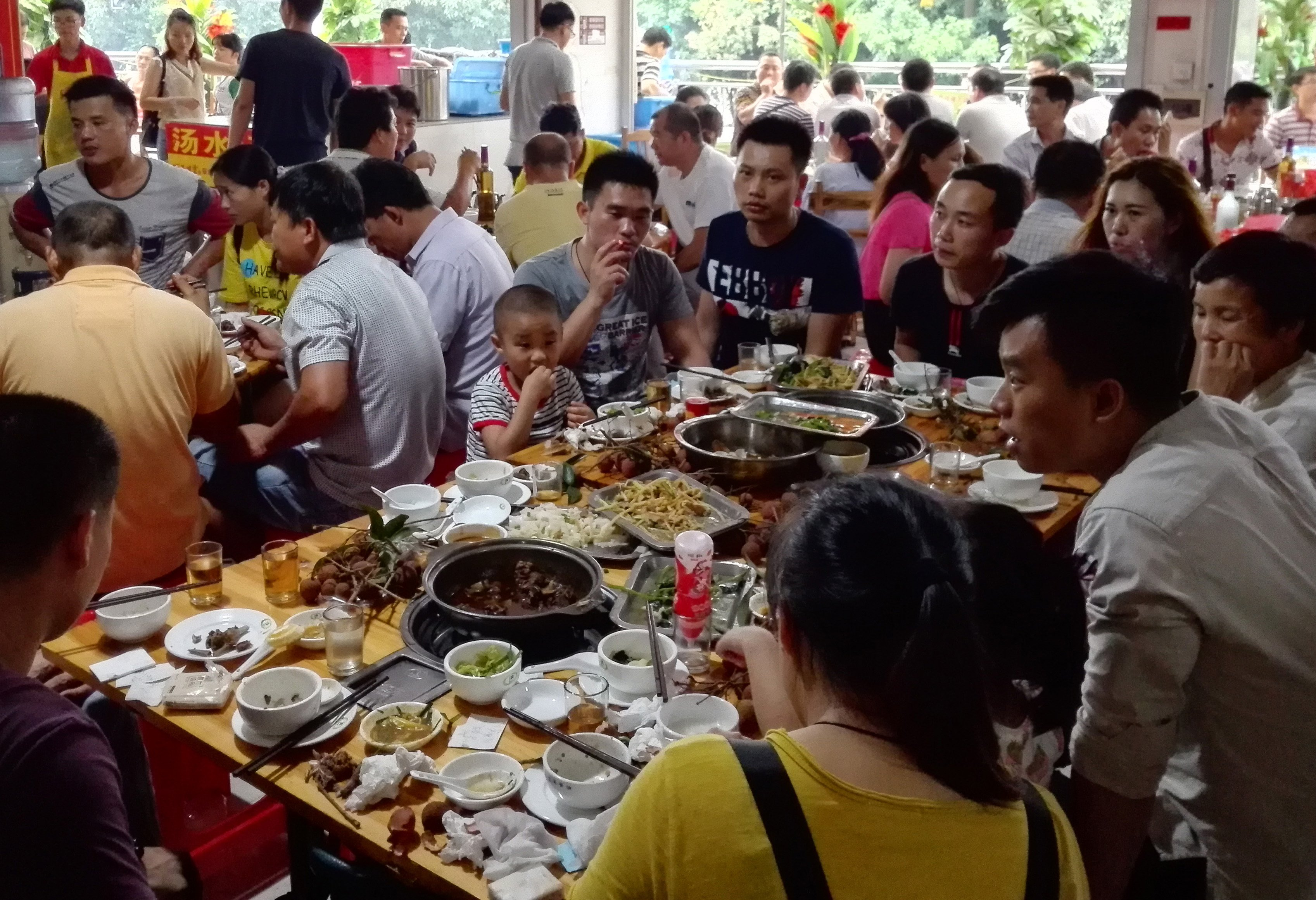 People eat dog meat at a restaurant in Yulin, in China's southern Guangxi region on June 21, 2017. China's most notorious dog meat festival opened in Yulin on June 21, 2017, with butchers hacking slabs of canines and cooks frying the flesh following rumours that authorities would impose a ban this year. (Photo credit should read STR/AFP via Getty Images)