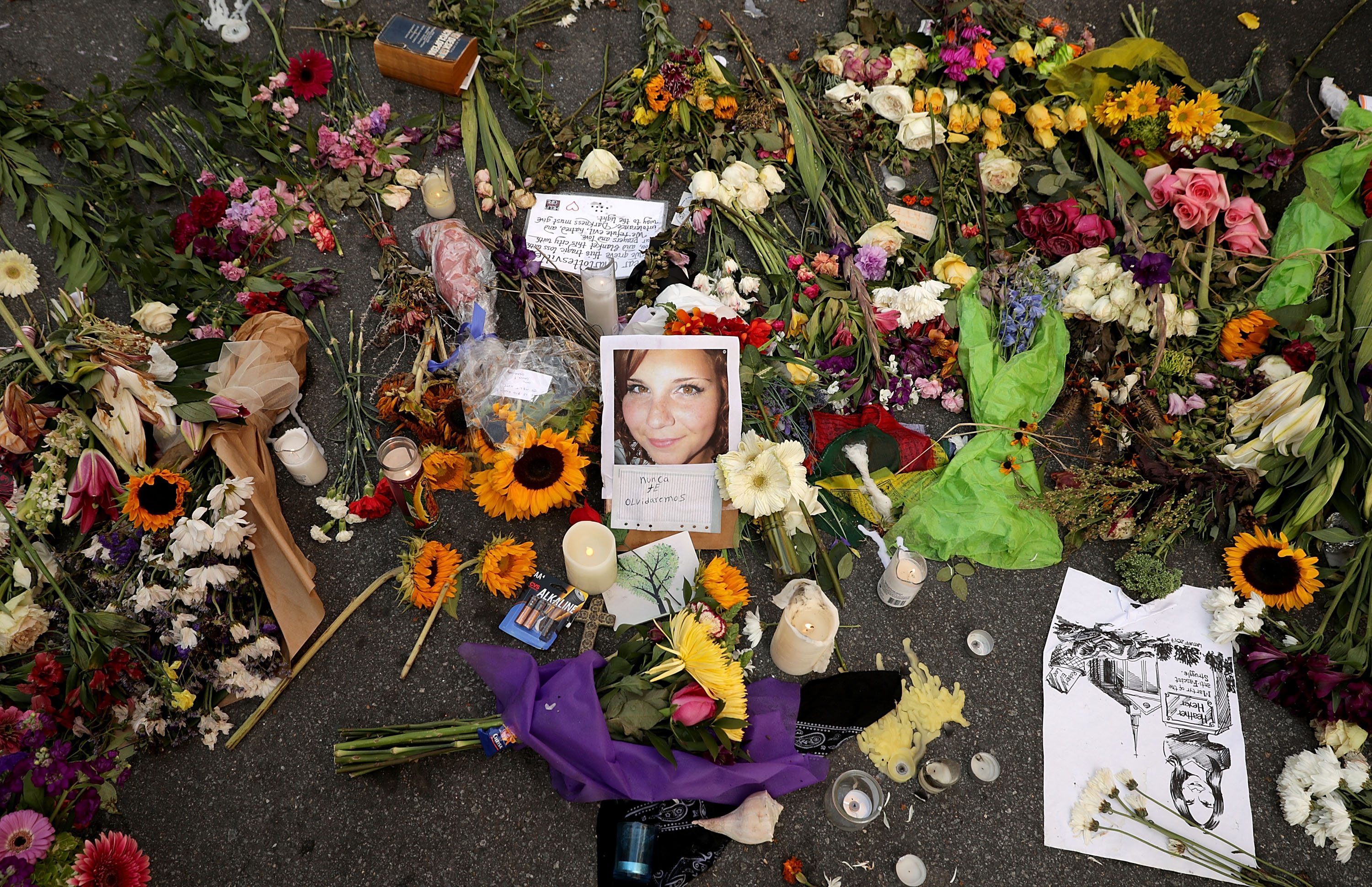Flowers, candles and chalk-written messages surround a photograph of Heather Heyer on the spot where she was killed and 19 others injured when a car slamed into a crowd of people protesting against a white supremacist rally, August 16, 2017 in Charlottesville, Virginia. (Photo by Chip Somodevilla/Getty Images)