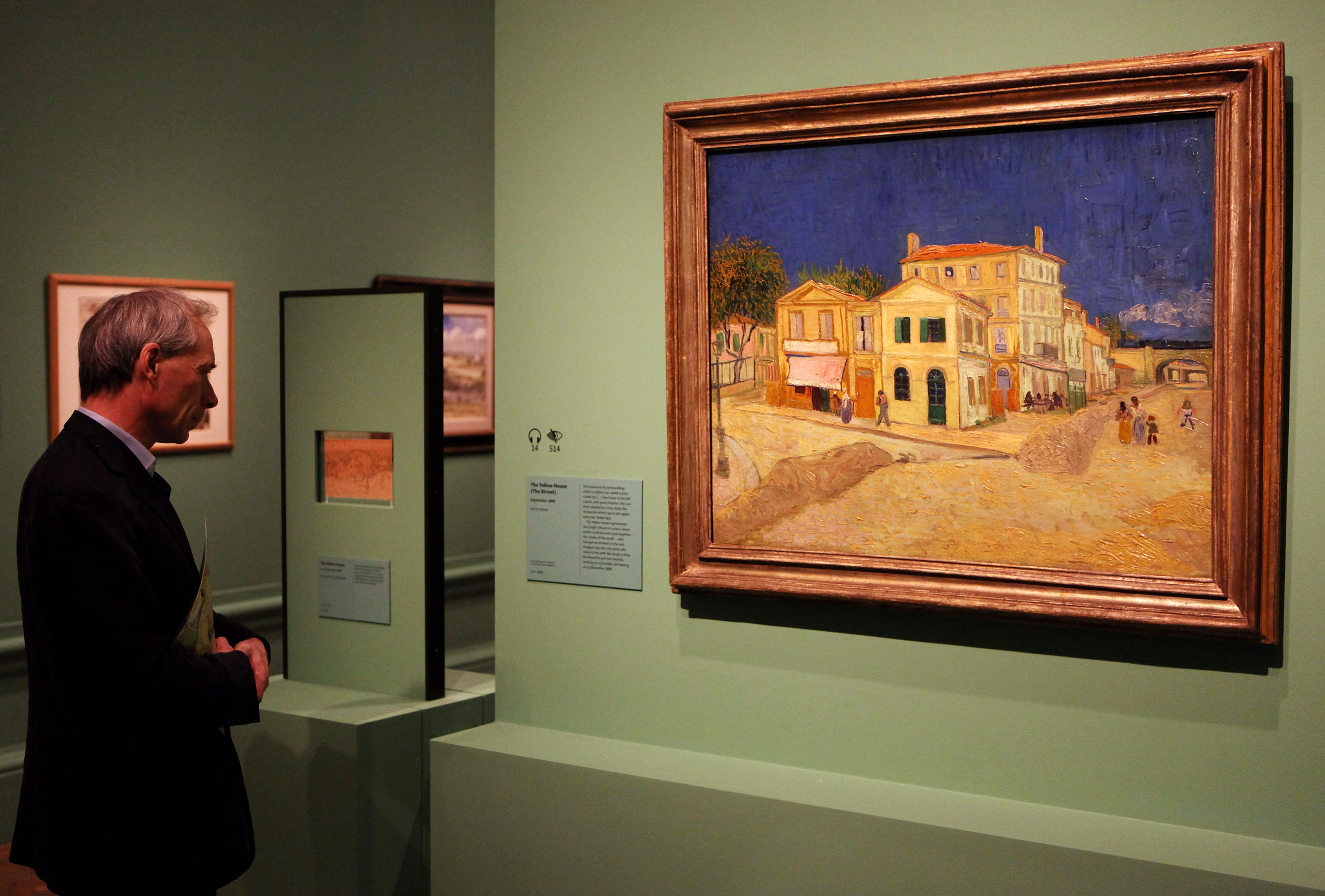 """A man admires an oil painting by acclaimed Dutch artist Vincent Van Gogh entitled """"The Yellow House (The Street)"""" in an exhibition of his work held at the Royal Academy of Arts on January 19, 2010 in London, England. (Photo by Oli Scarff/Getty Images)"""