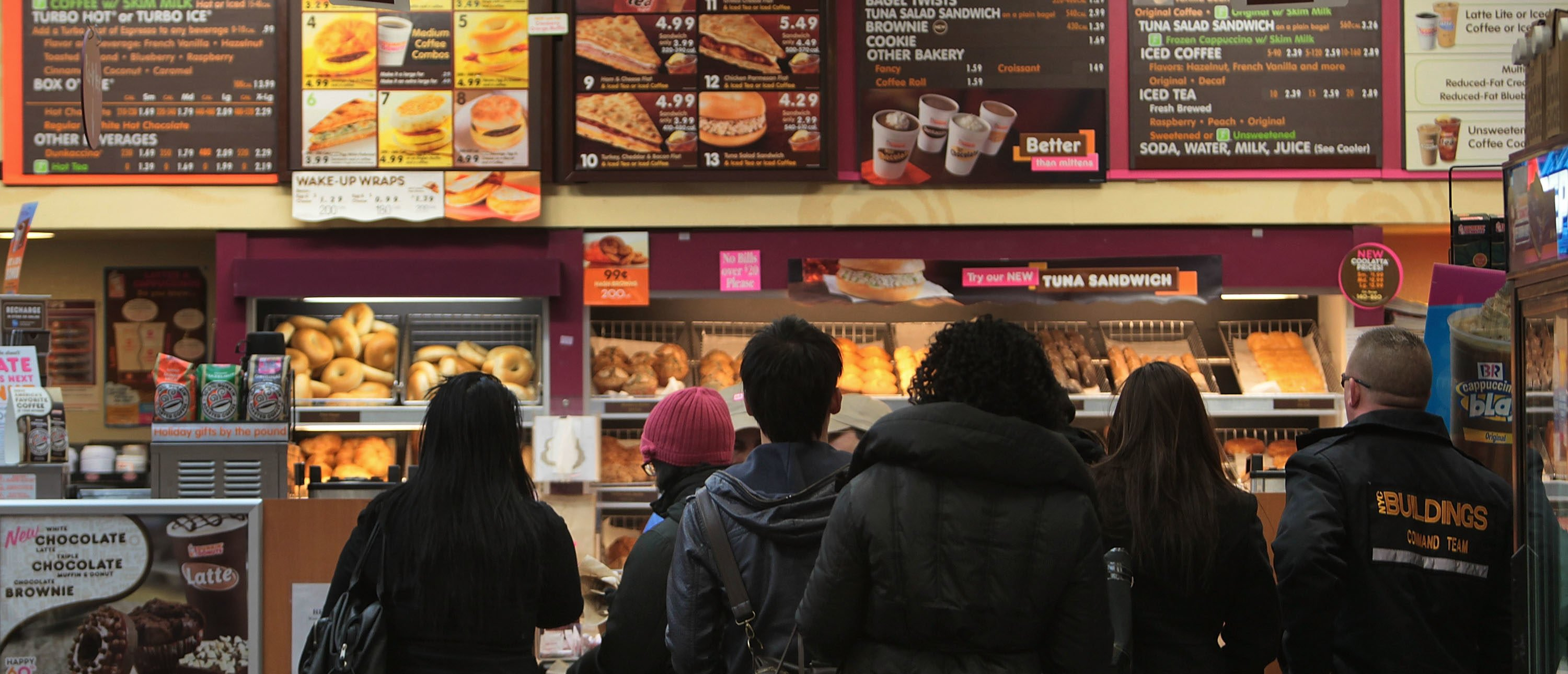NEW YORK - FEBRUARY 22: People wait in line in the morning at a Dunkin' Donuts chain restaurant February 22, 2010 in New York City. Restaurant breakfast sales across the country are down sharply, and analysts blame the troubled economy for the dip as fewer Americans go to work in the mornings. (Photo by Chris Hondros/Getty Images)