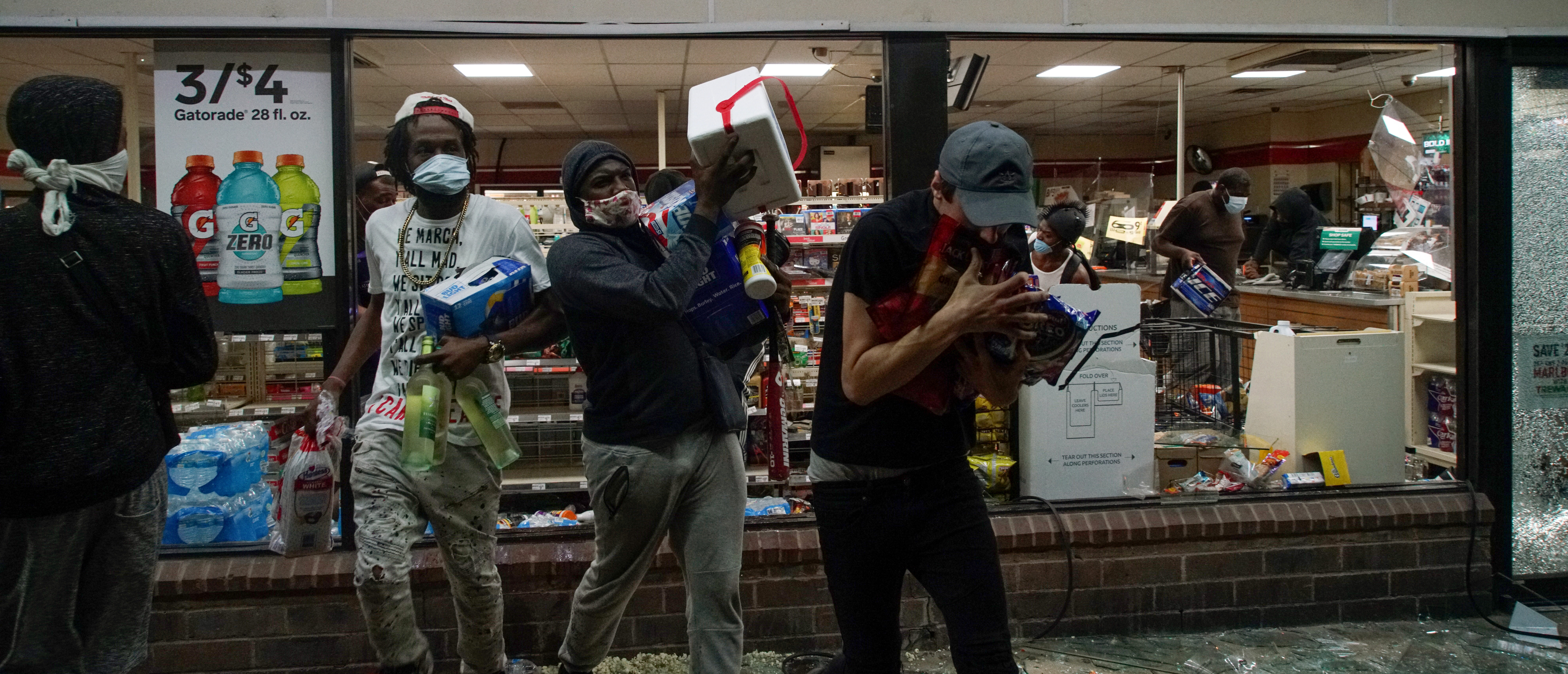 Looters come out a broken window of a 7-11 during a protest against the death in Minneapolis police custody of African-American man George Floyd, in St Louis, Missouri, U.S., June 1, 2020. REUTERS/Lawrence Bryant