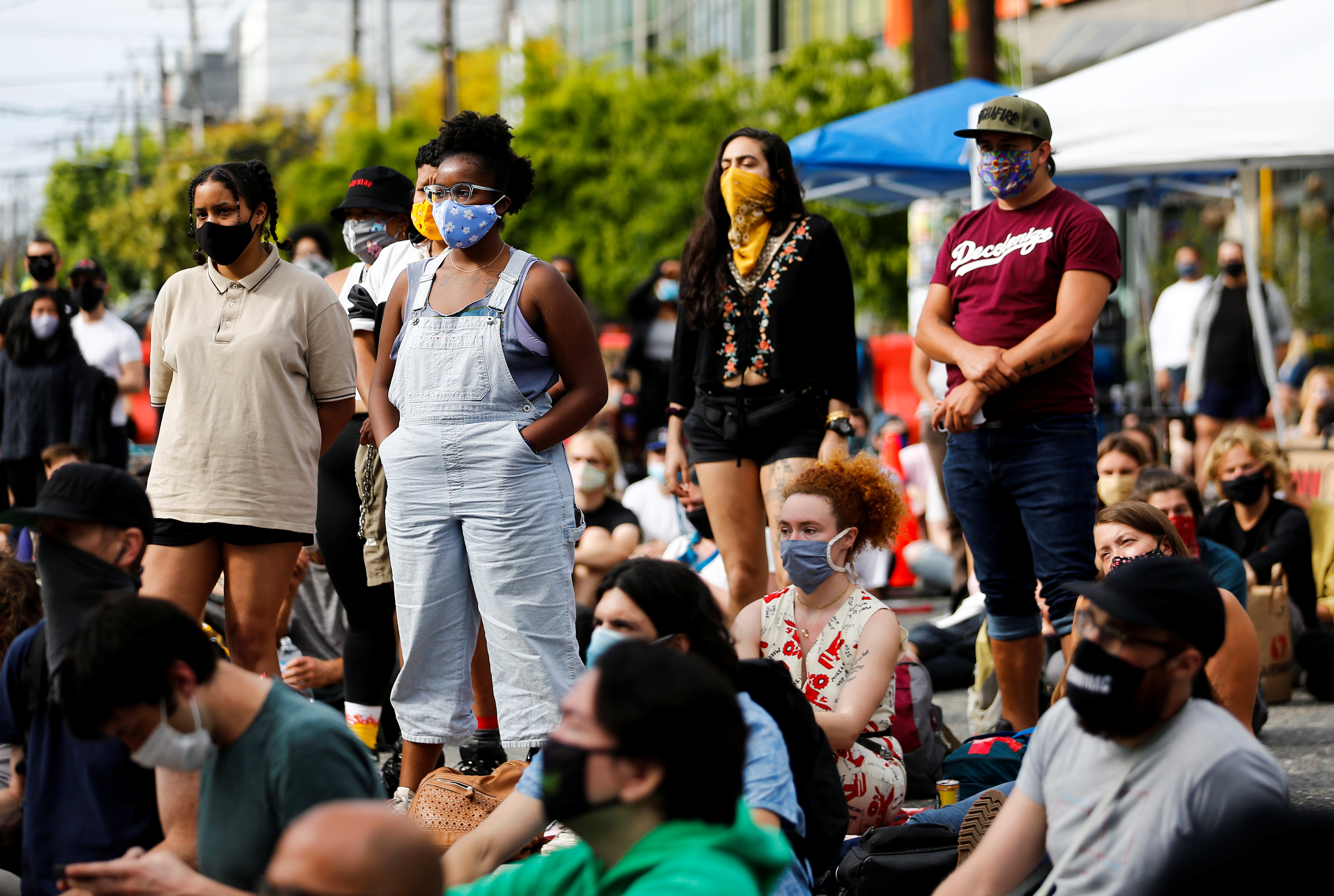 Protesters who identify as people of color stand as a speaker encourages white attendees to sit as protesters establish what they call an autonomous zone while continuing to protest against racial inequality and call for a defunding of Seattle police, in Seattle, Washington, U.S. June 10, 2020. (REUTERS/Lindsey Wasson)