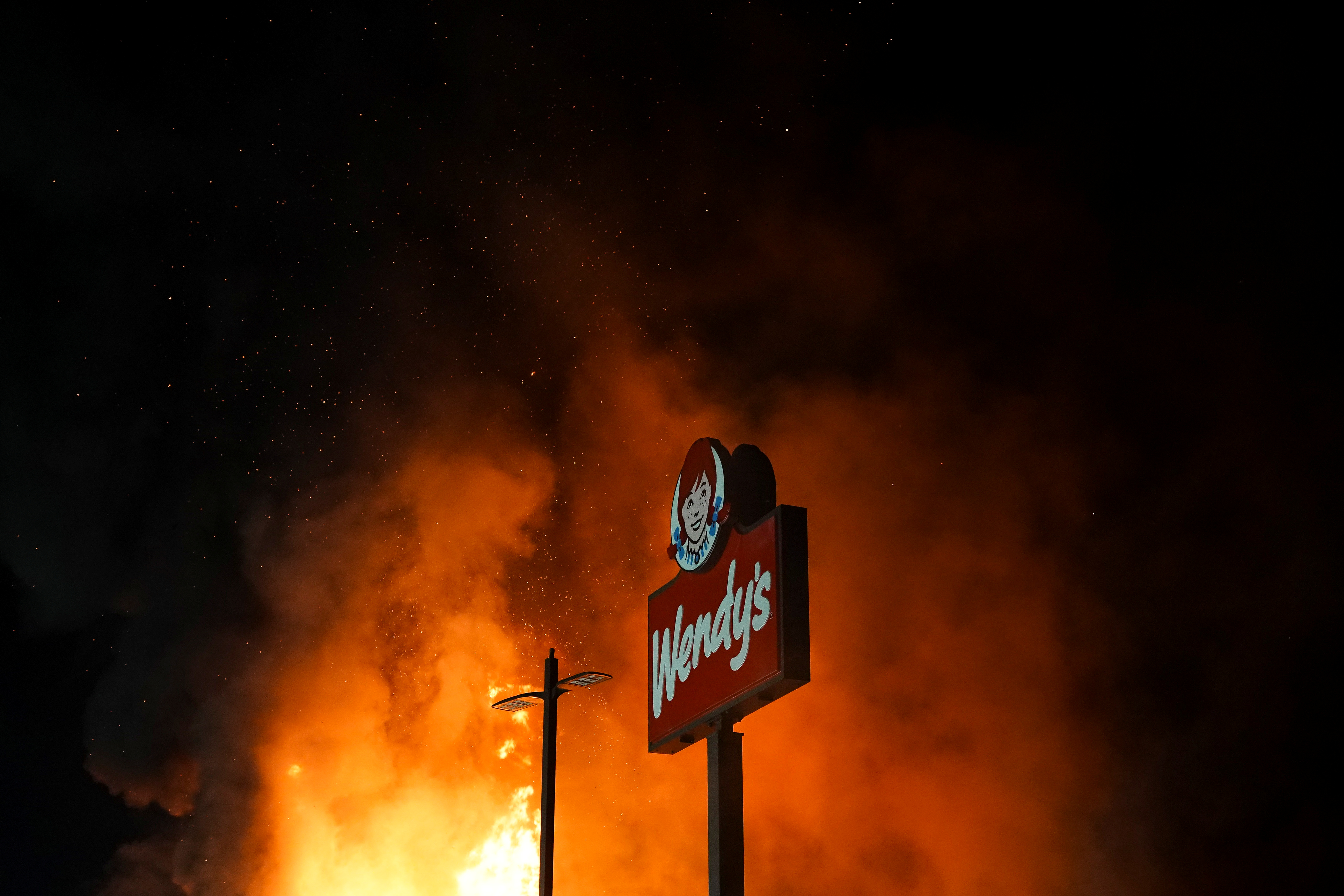 A Wendy's burns following a rally against racial inequality and the police shooting death of Rayshard Brooks, in Atlanta, Georgia, U.S. June 13, 2020. REUTERS/Elijah Nouvelage