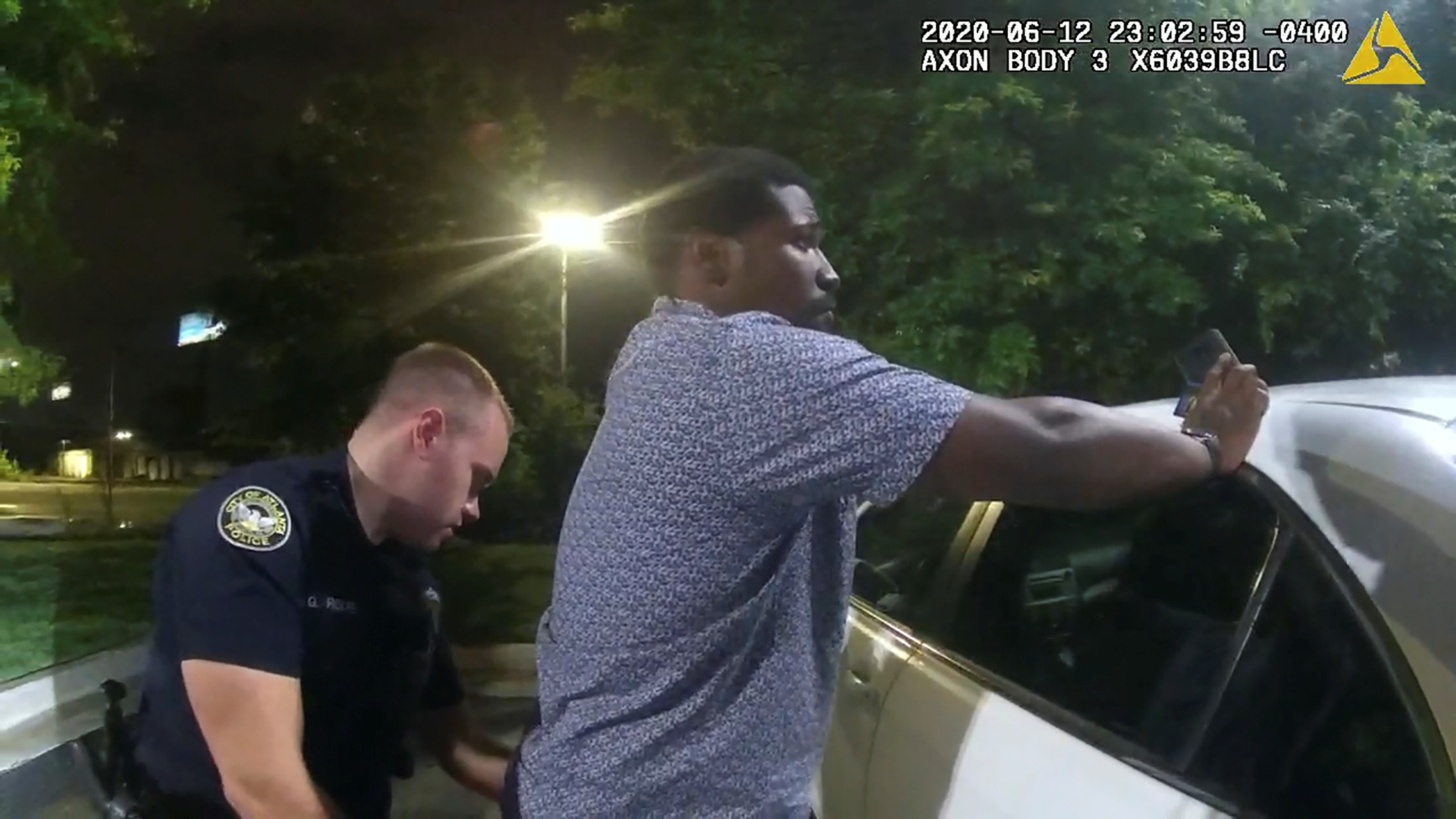 Former Atlanta Police Department officer Garrett Rolfe searches 27-year-old Rayshard Brooks in a Wendy's restaurant parking lot in a still image from the video body camera of officer Devin Bronsan in Atlanta, Georgia, U.S. June 12, 2020. Video taken June 12, 2020. Atlanta Police Department/Handout via REUTERS.